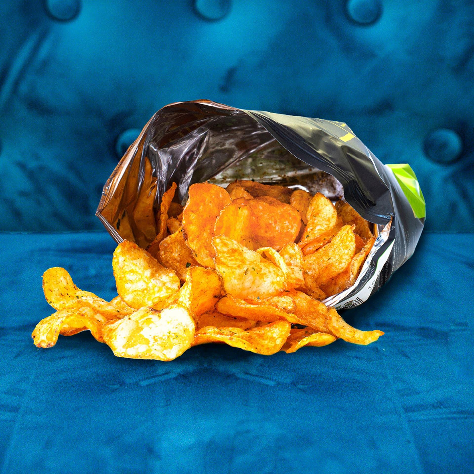 Eine Tüte Chips auf blauem Sofa