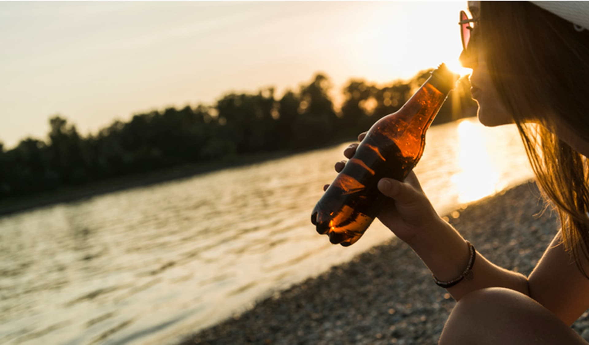 Eine Frau trinkt Malzbier bei Sonnenuntergang am See