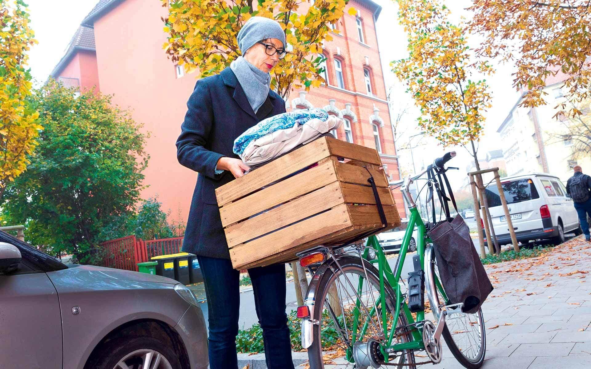 Frau packt Kleidung in einer Kiste auf ihren Fahrrad-Gepäckträger.