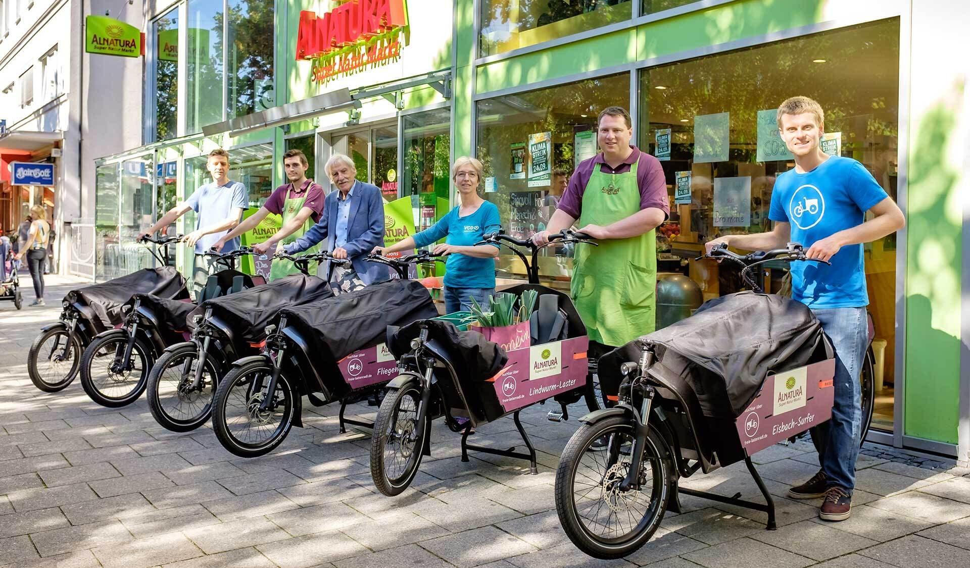 Alnatura-Mitarbeiter mit Lastenrädern vor einem Super Natur Markt