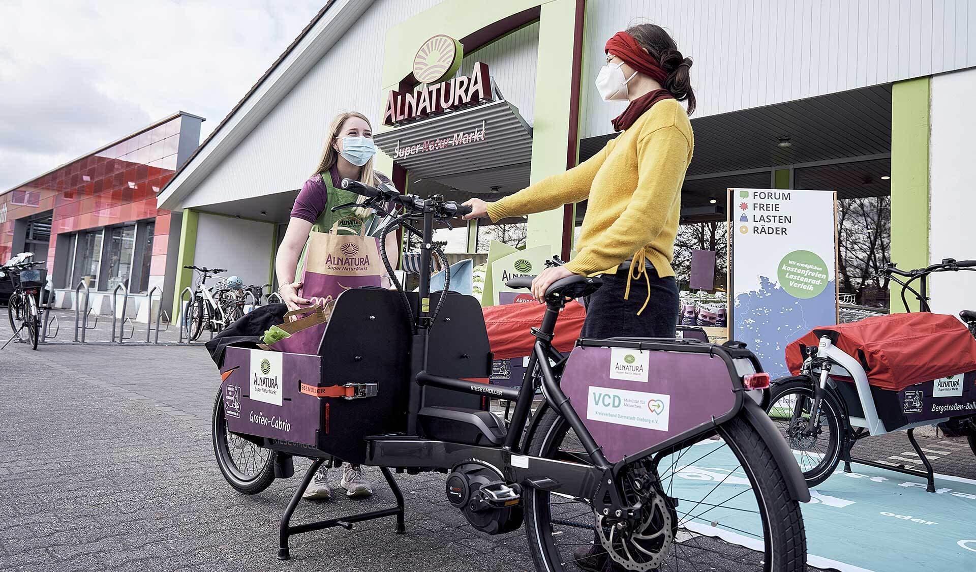 Zwei Frauen mit Lastenrad vor Alnatura Super Natur Markt