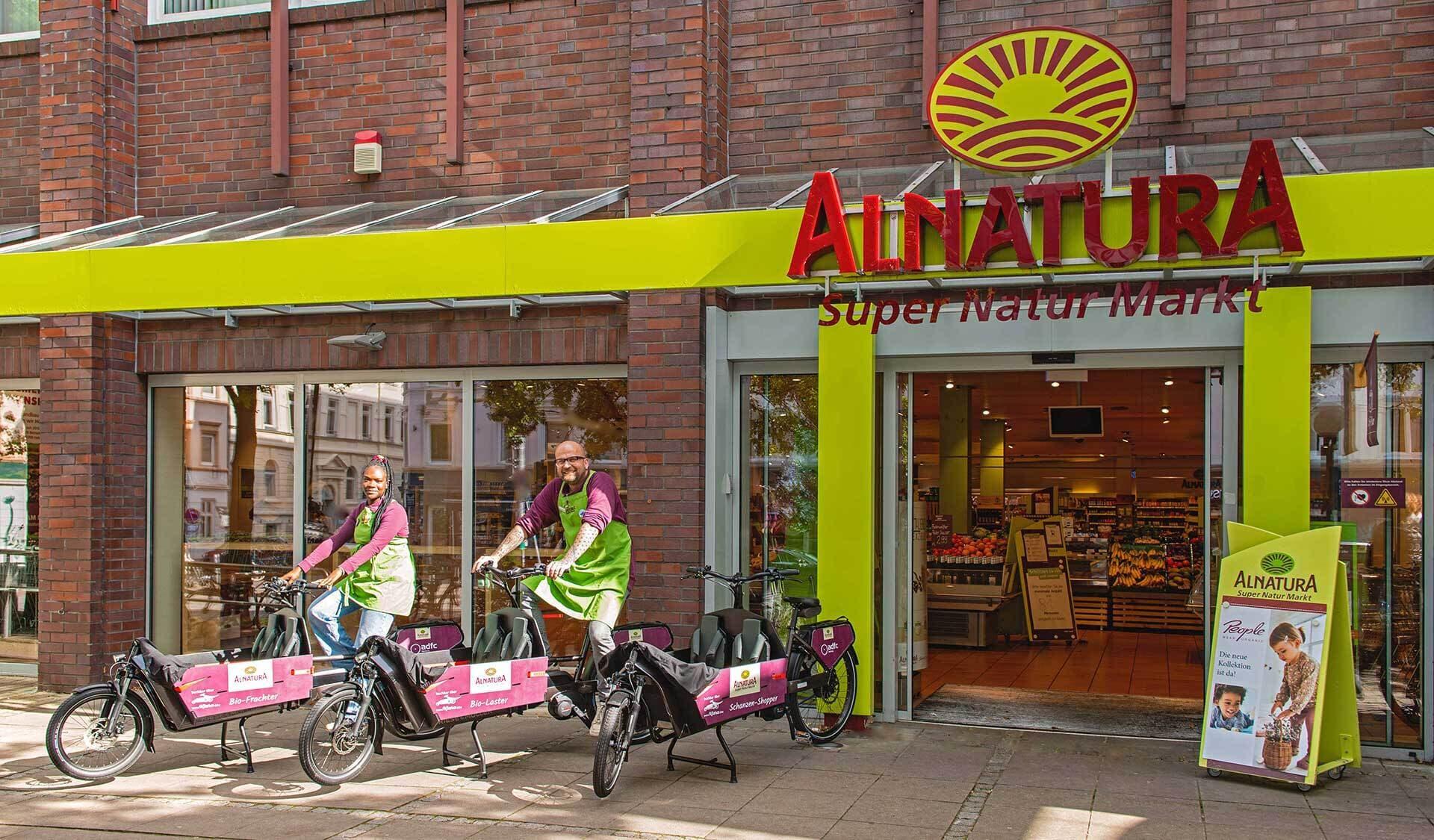 Zwei personen auf je einem Lastenrad vor Alnatura Super Natur Markt