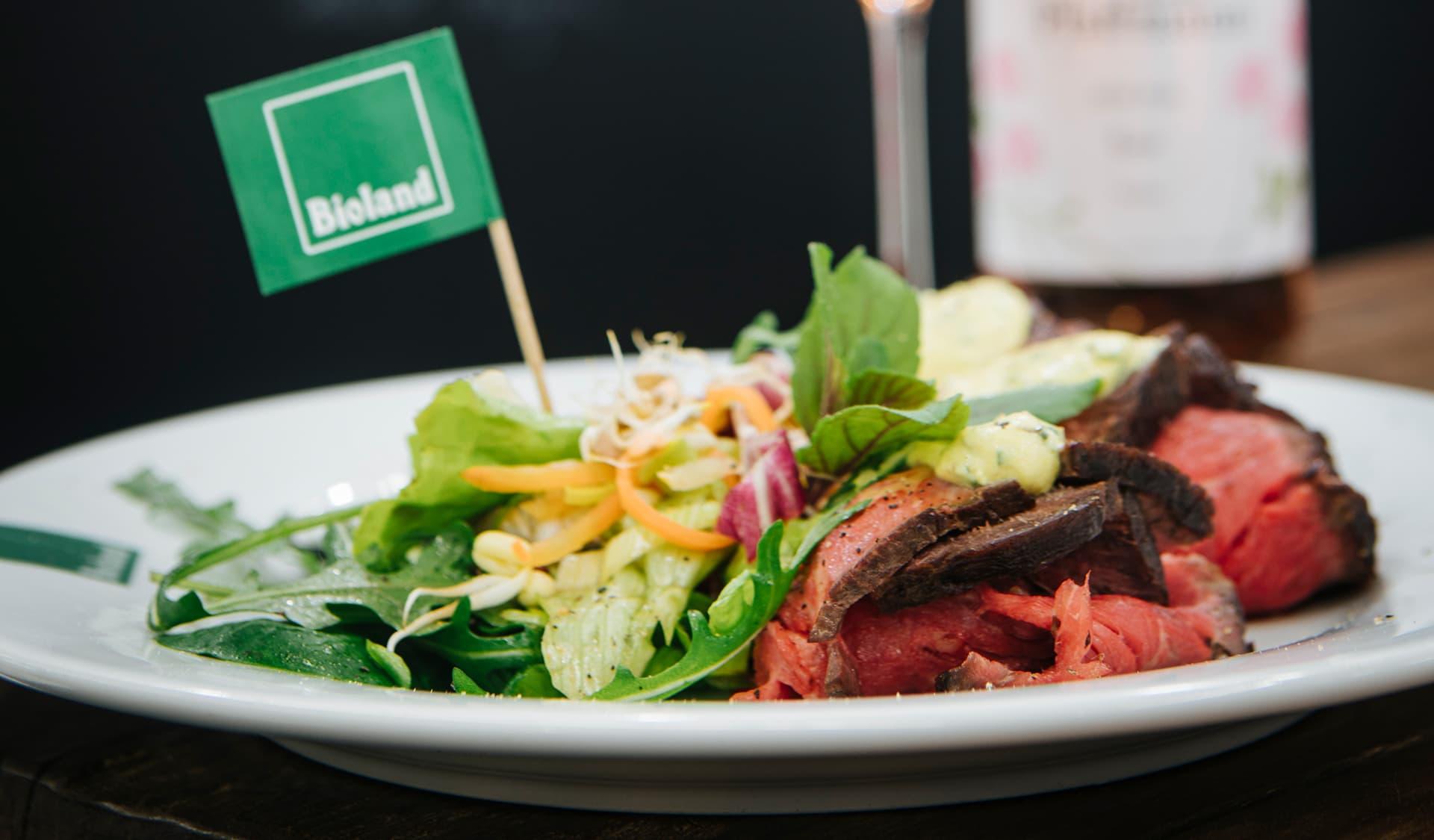 Salat und Rindfleisch auf einem Teller mit Bioland-Fähnchen