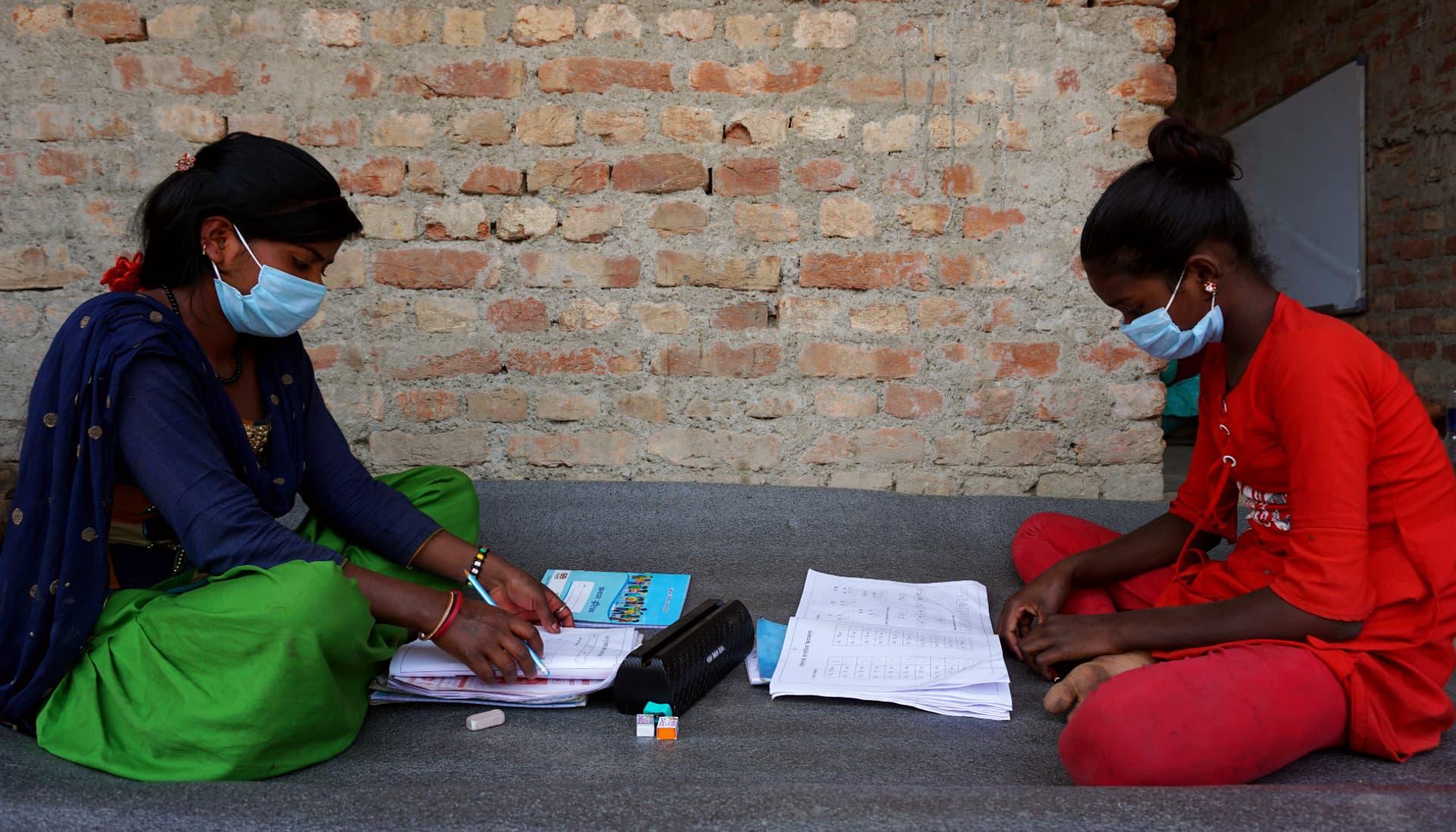 Zwei Mädchen sitzen auf dem Boden und lernen