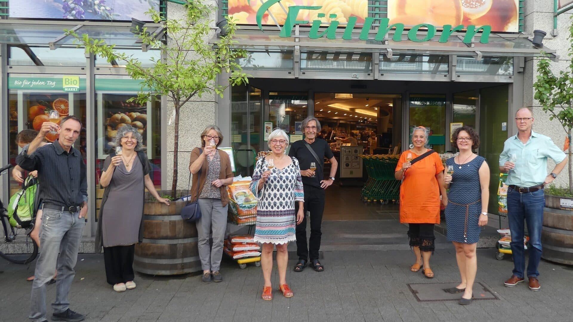 Genossinnen und Genossen vor dem Laden mit Sektgläsern
