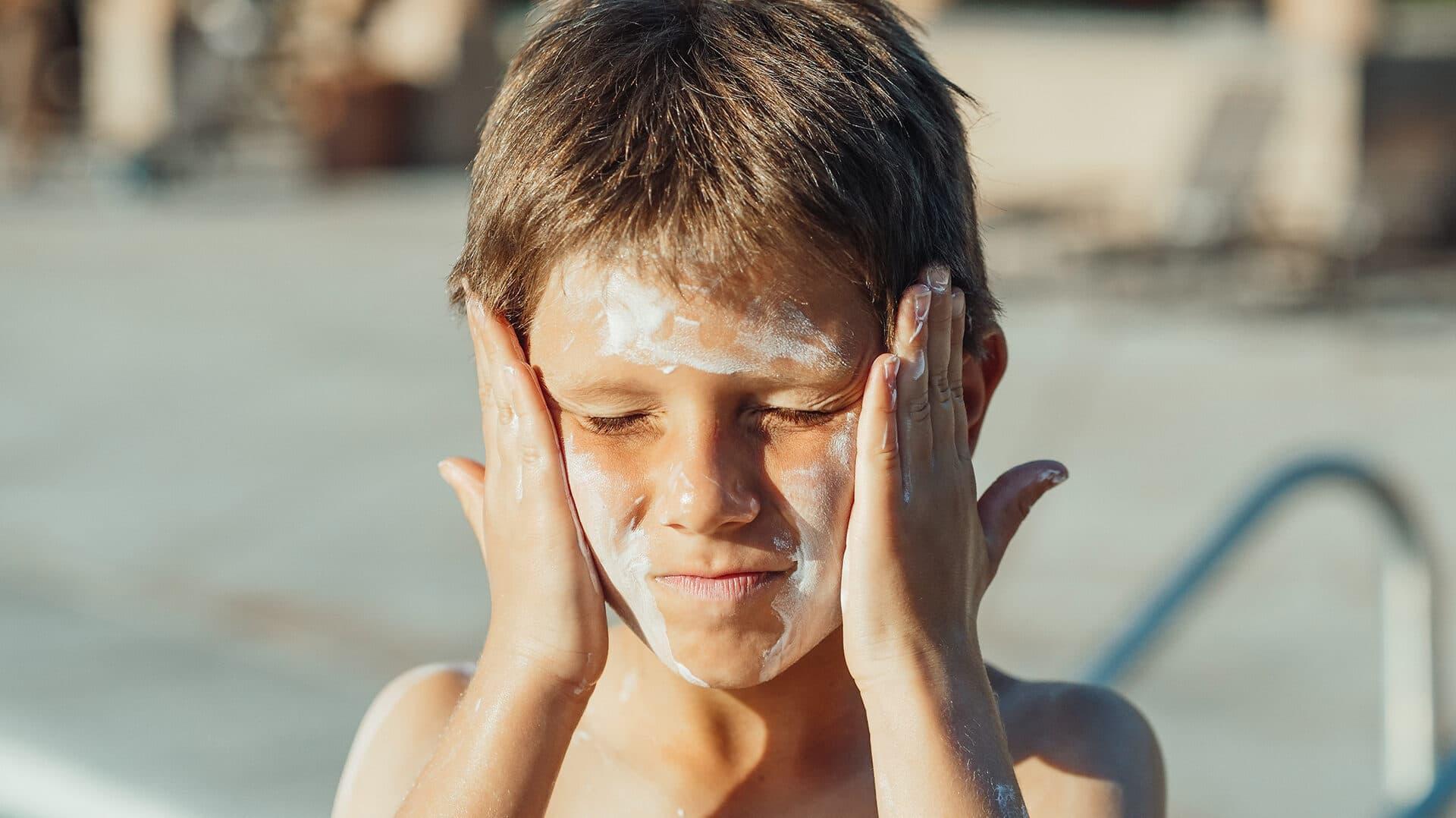 Junge verteilt Sonnencreme in seinem Gesicht