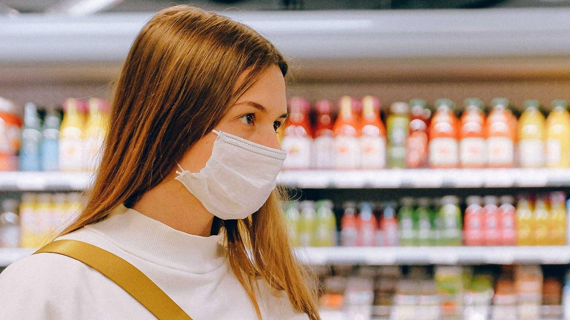 Kundin mit Mund-Nasen-Schutz im Lebensmittelgeschäft