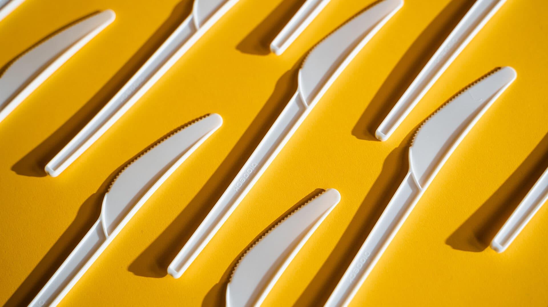 Weiße Plastikmesser auf gelben Untergrund