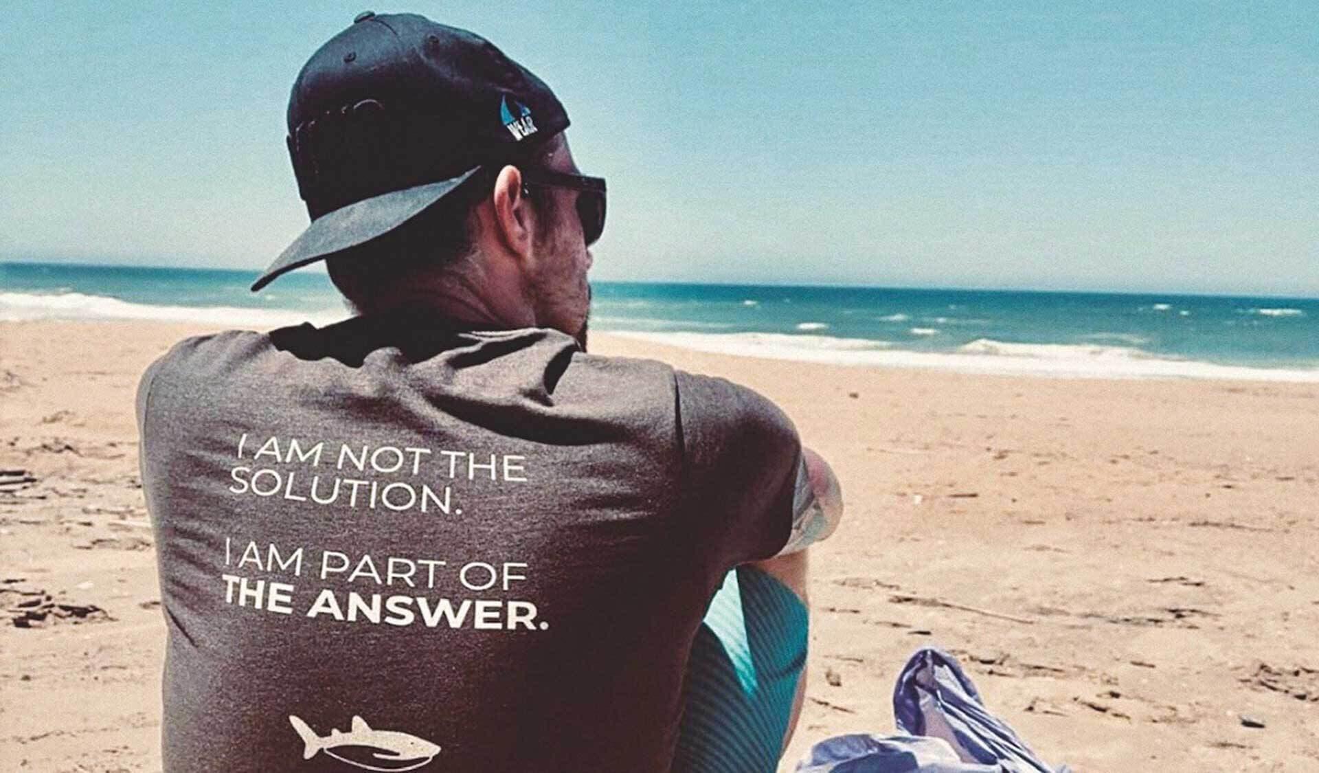 Ozeankind-Mitgründer Michael Schmidt sitzen, von hinten, am Strand