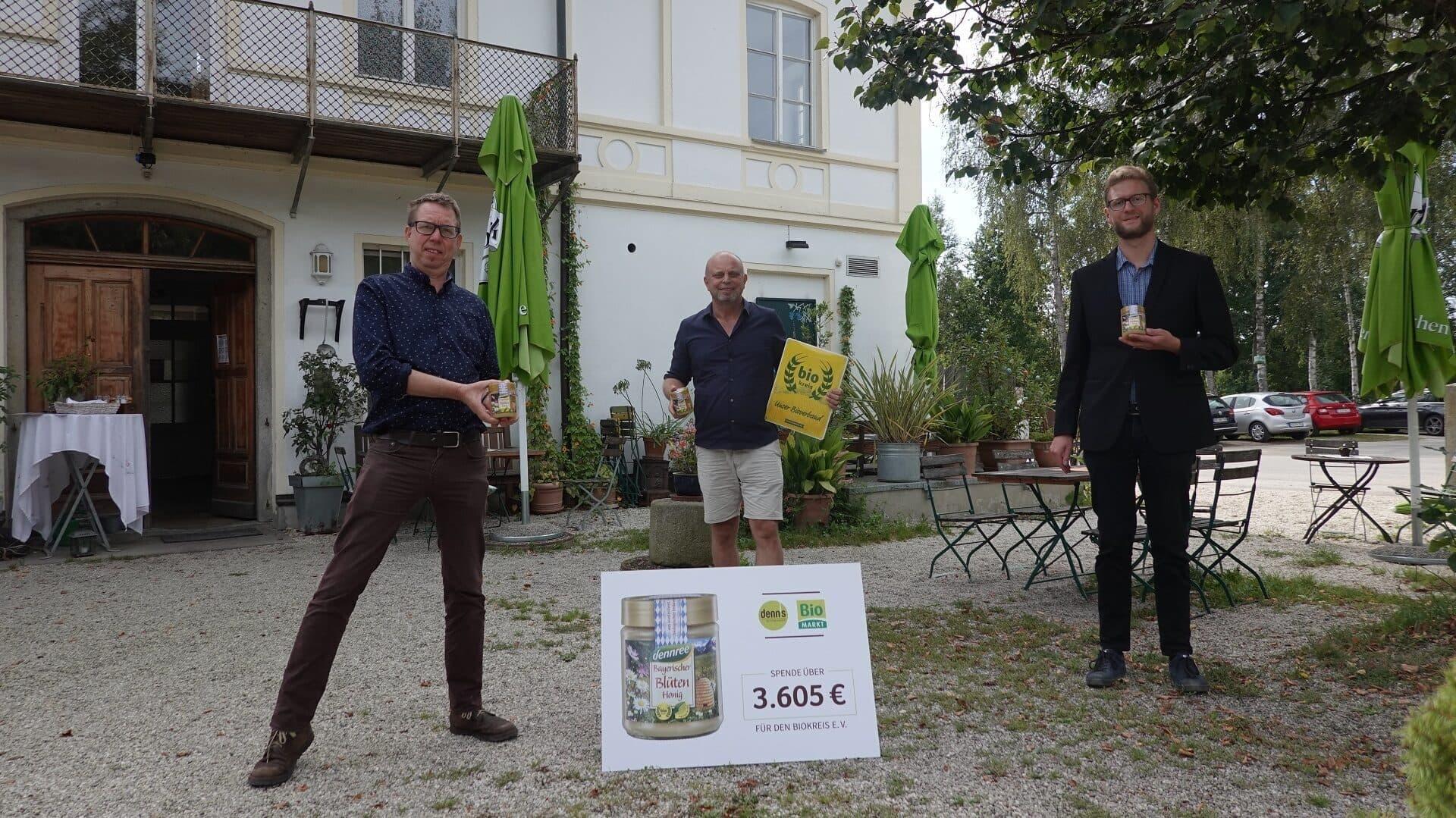 Marc Schüller (Imkerberater Biokreis, links) und Sepp Brunnbauer (Geschäftsführer Biokreis) nehmen die Spende von Adrian Knirlberger (Interessengemeinschaft Biomarkt) entgegen.