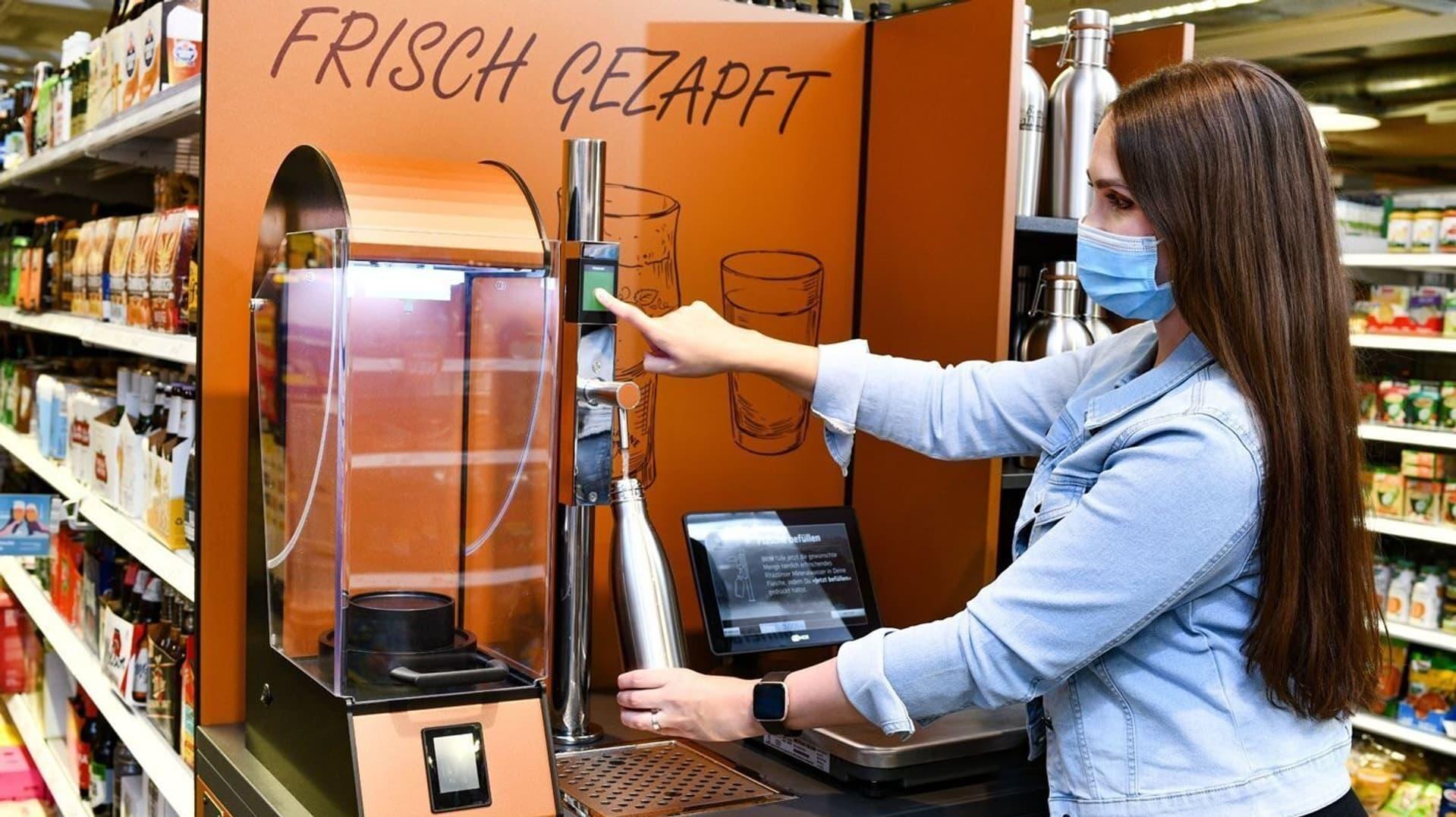 Kundin mit Mundschutz an Abfüllstation für Bier und Wasser