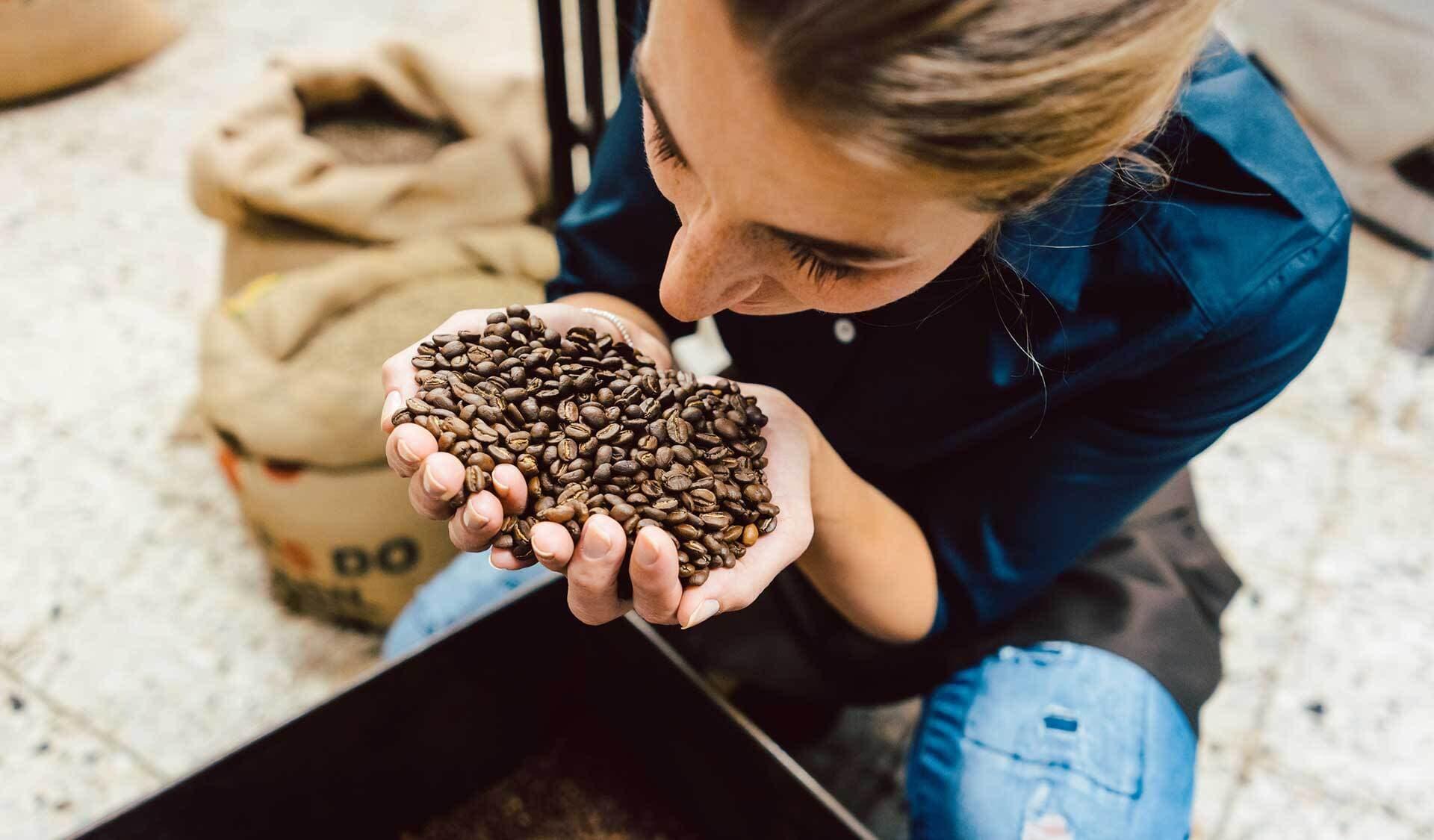 Frau mit zwei Händen voll Kaffeebohnen