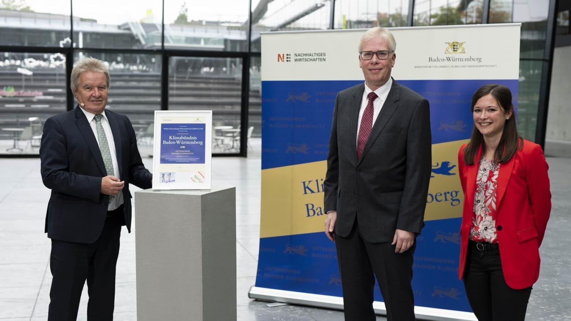 Umweltminister Franz Untersteller (links) die Urkunde an Dr. Thilo Haßler (Leiter Wissenschaft Schoenenberger) und Cassandra Heimgartner (Nachhaltigkeitsbeauftragte Schoenenberger)