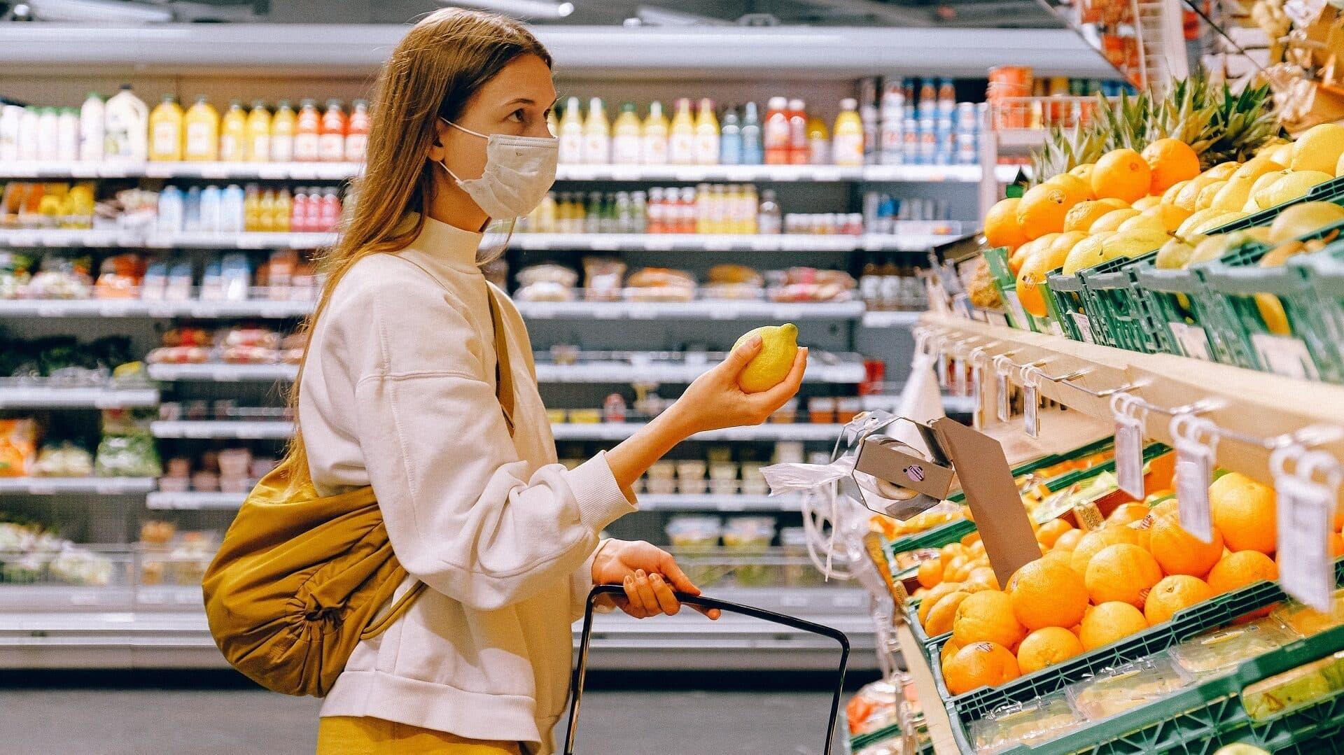 Junge Frau mit Mundschutz beim Lebensmitteleinkauf