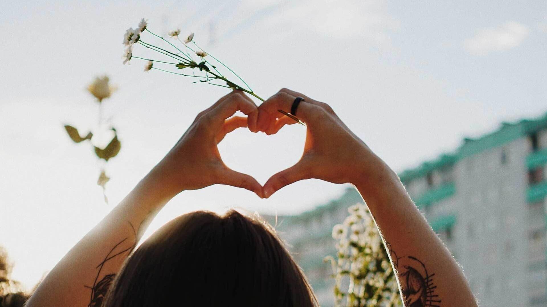 Frau formt Herz mit ihren Händen