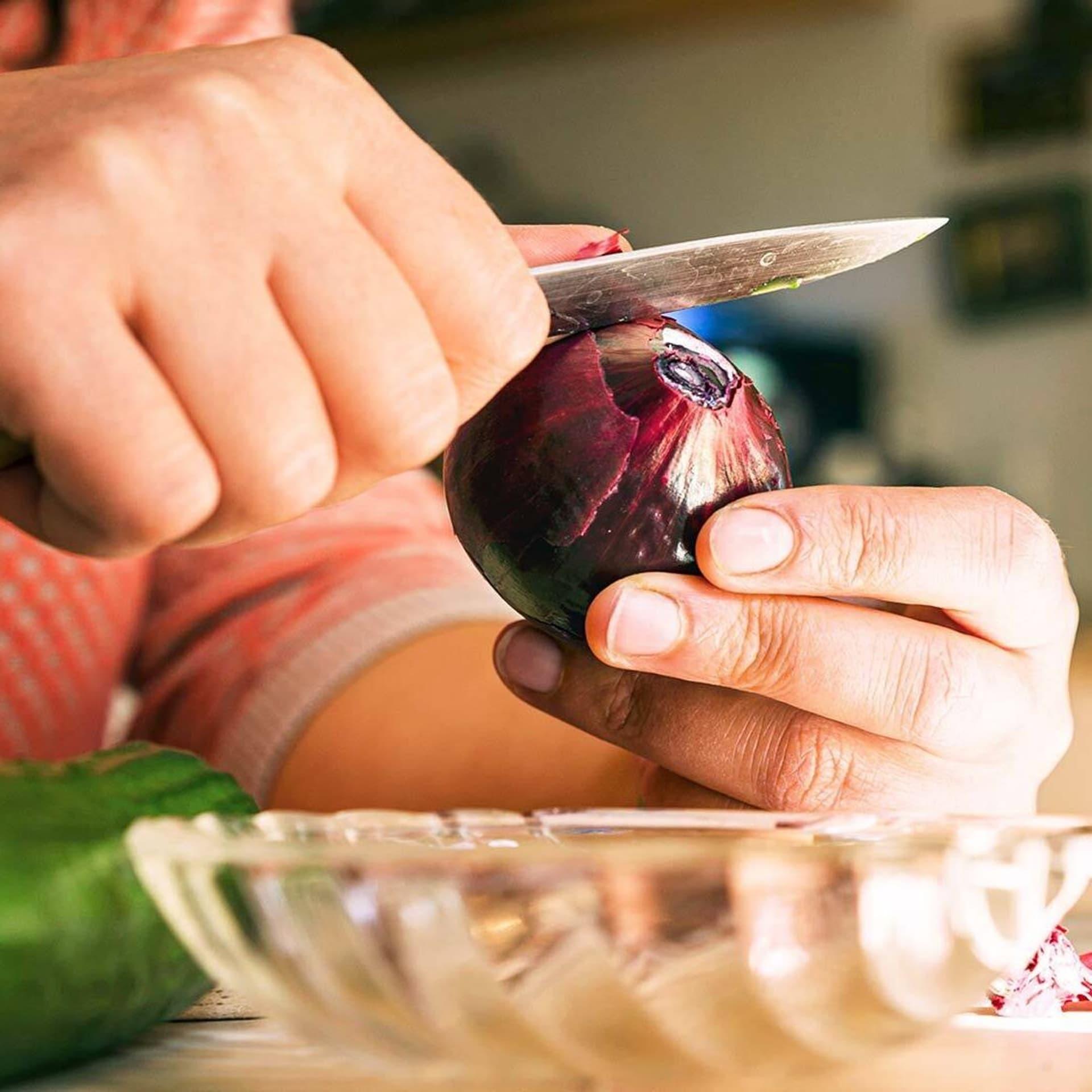 Frau entfernt Schale einer roten Zwiebeln