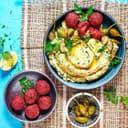 Rote Bete Falafel an Kraeuter Hummus auf Tellern angerichtet