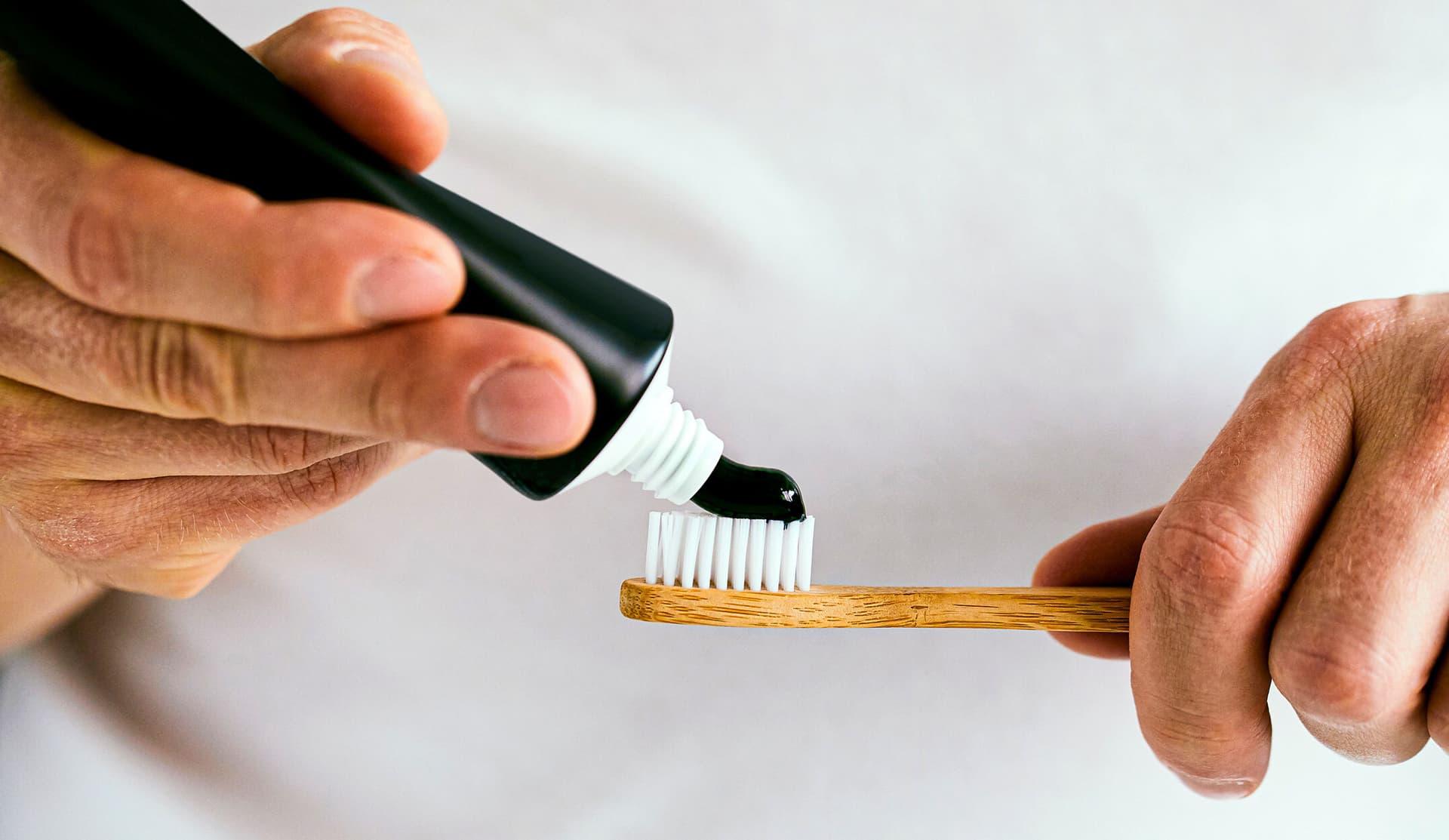 Schwarze Zahncreme wird aus einer Tube auf die Borsten einer Bambus-Zahnbürste gedrückt.