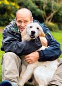 Thomas Henningsen sitzt auf einer Wiese und umarmt seinen Hund