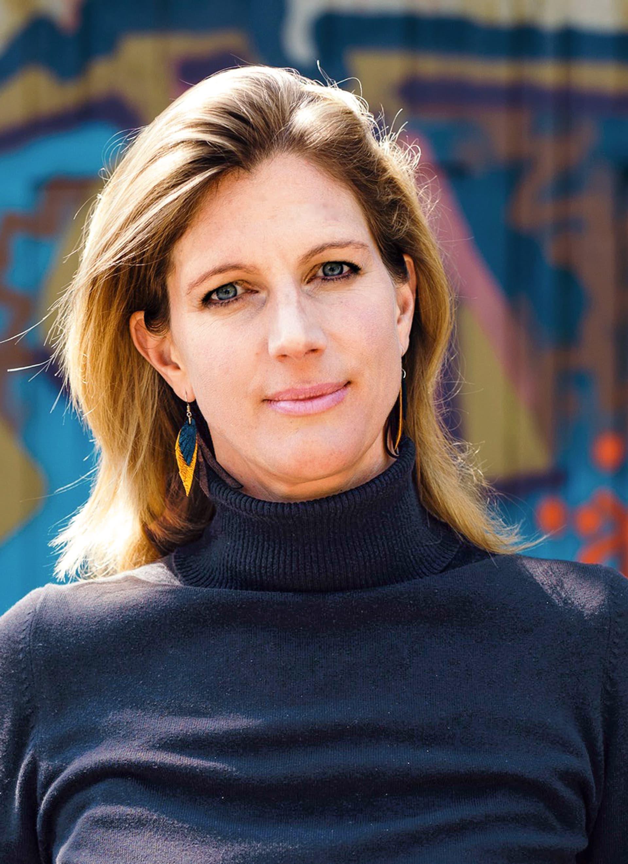 Porträtaufnahme von Maja Göpel im schwarzen Rollkragenpullover. Sie schaut in die Kamera. Im Hintergrund eine Graffiti.