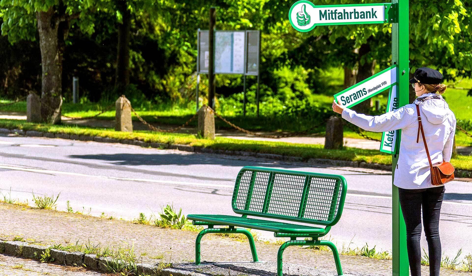 Eine Frau wartet bei der Mitfahrerbank und liest Schilder