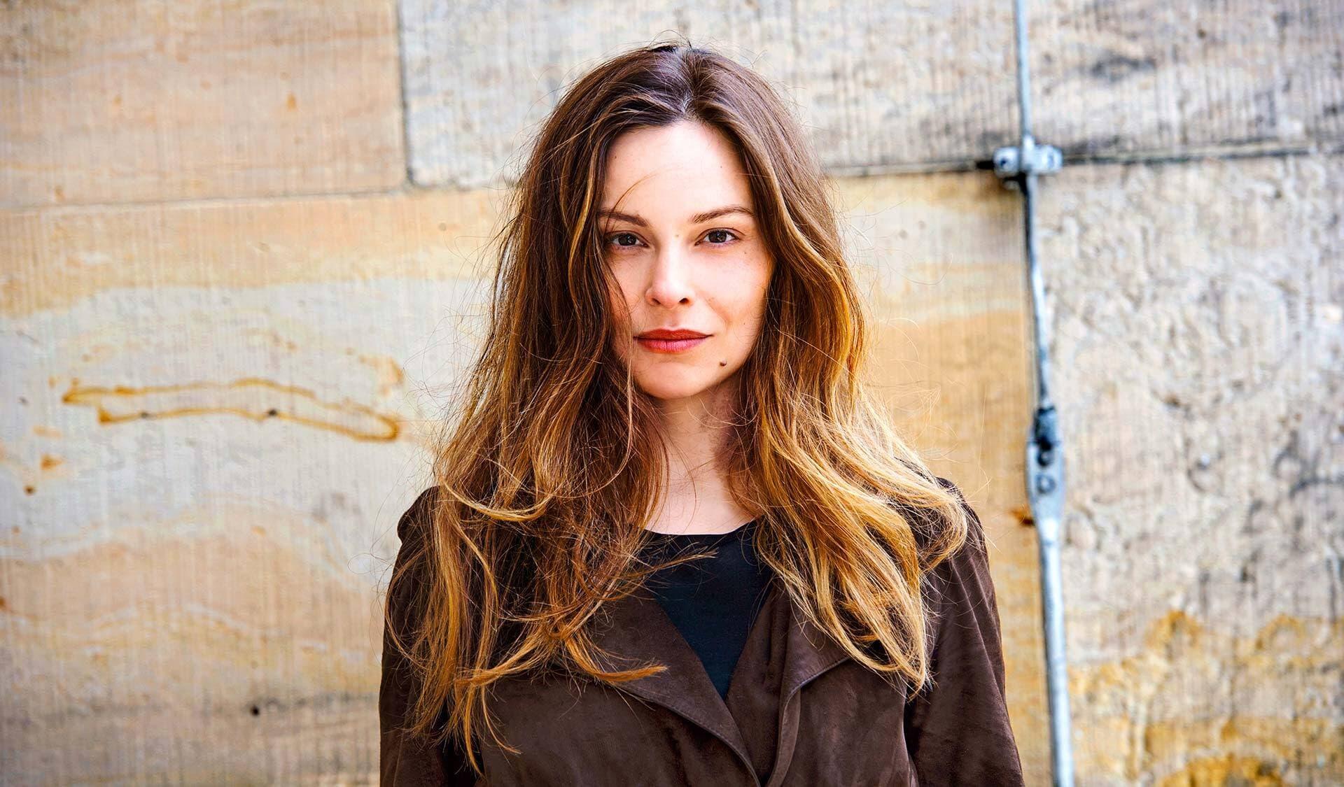 Schauspielerin Mina Tander, vor einer Wand stehend