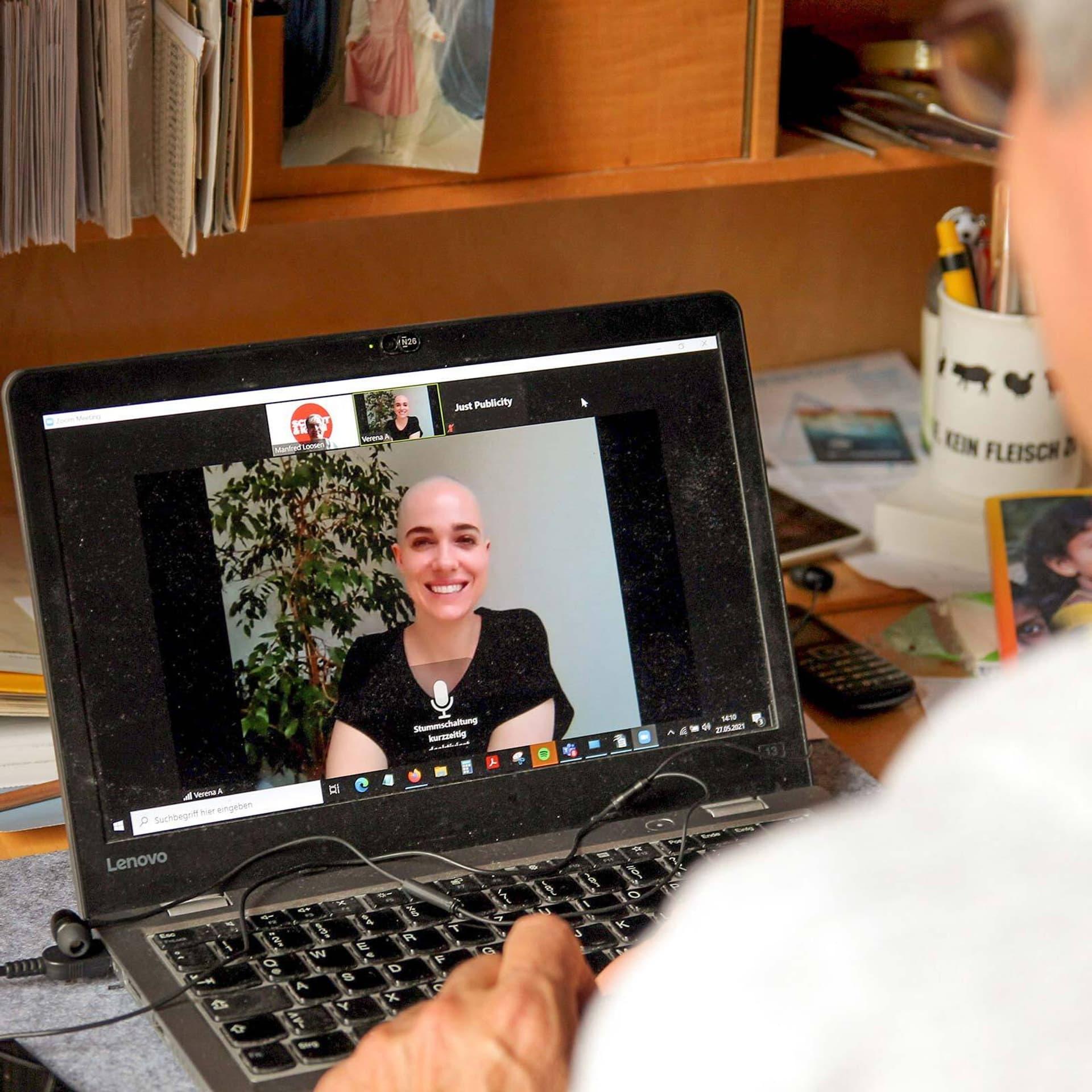Schauspielerin Verena Altenberger lächenld auf einem Computer-Bildschirm während des Online-Interviews.