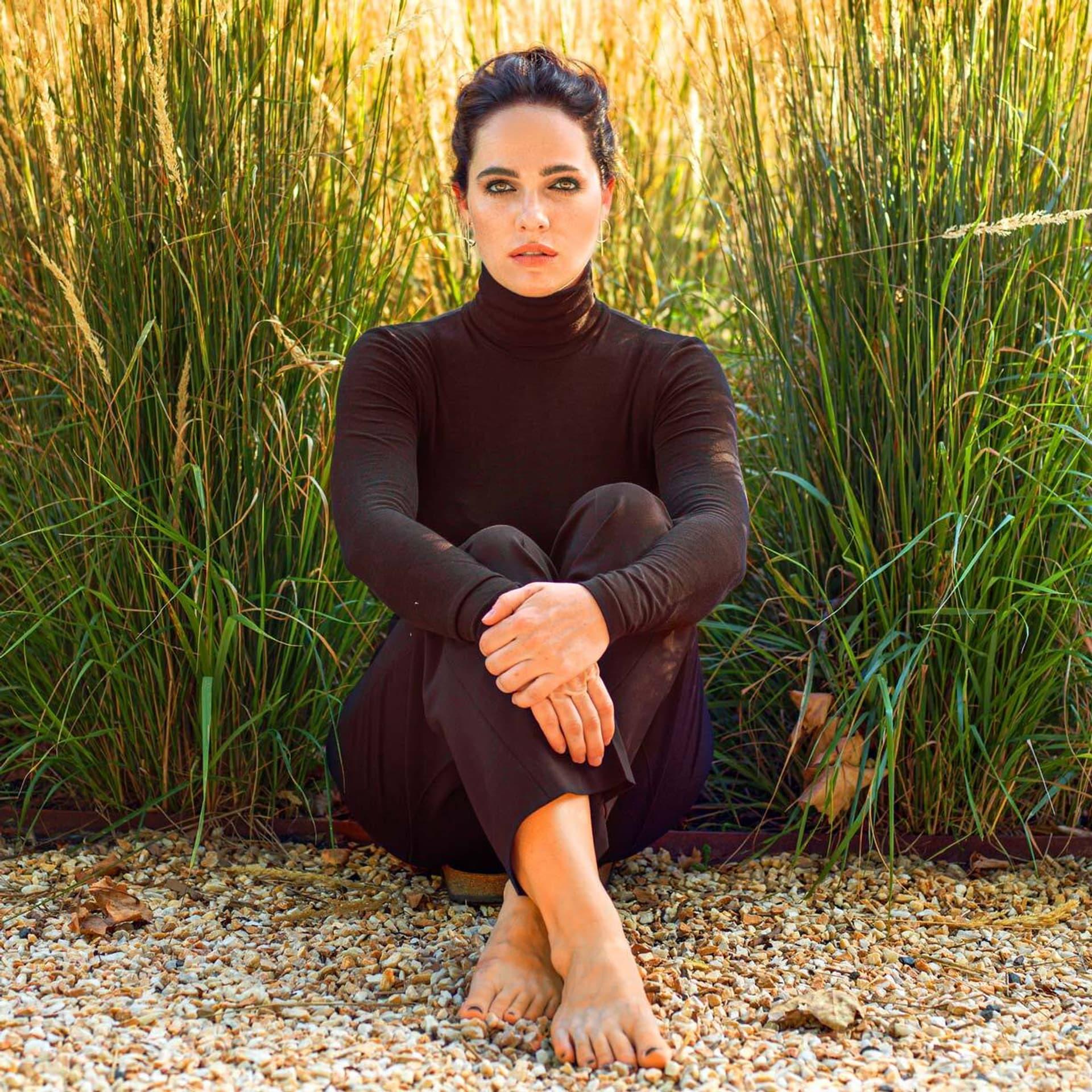 Schauspielerin Verena Altenberger, auf dem Boden sitzend, schaut in die Kamera.