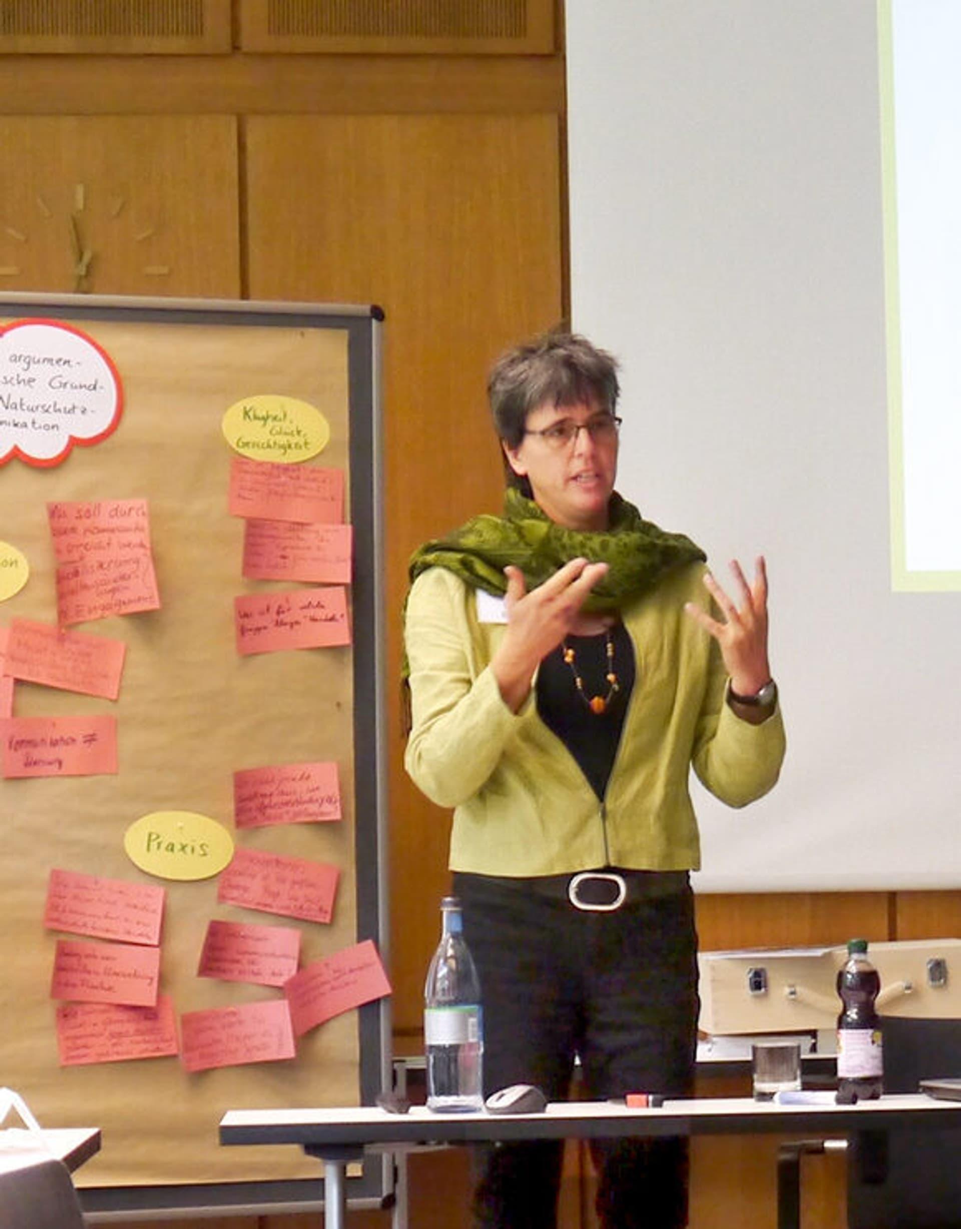 Uta Eser: Frau mit grüner Jacke und schwarzer Hose vor Flip-Chart