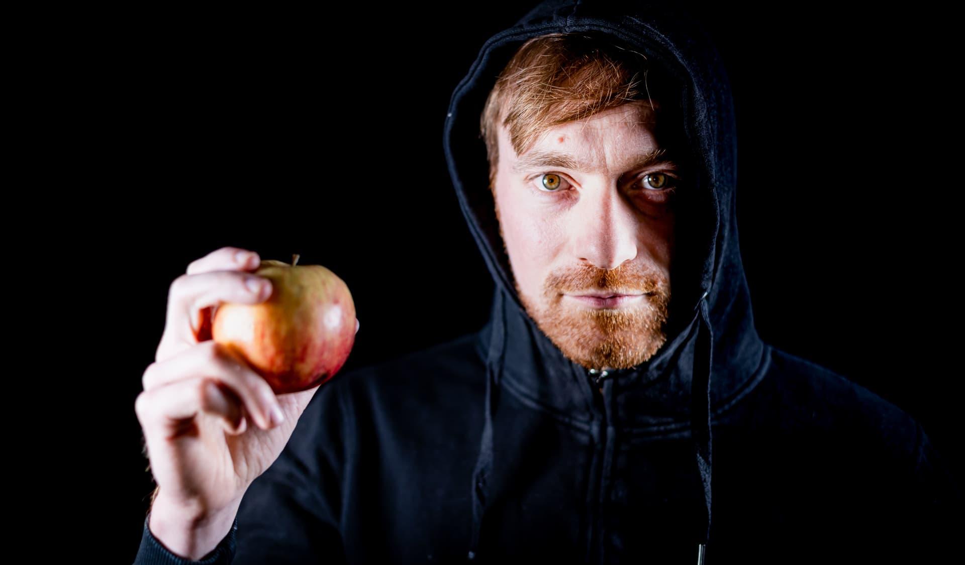 Umweltaktivist Karl Bär hält einen Apfel demonstrativ in der Hand