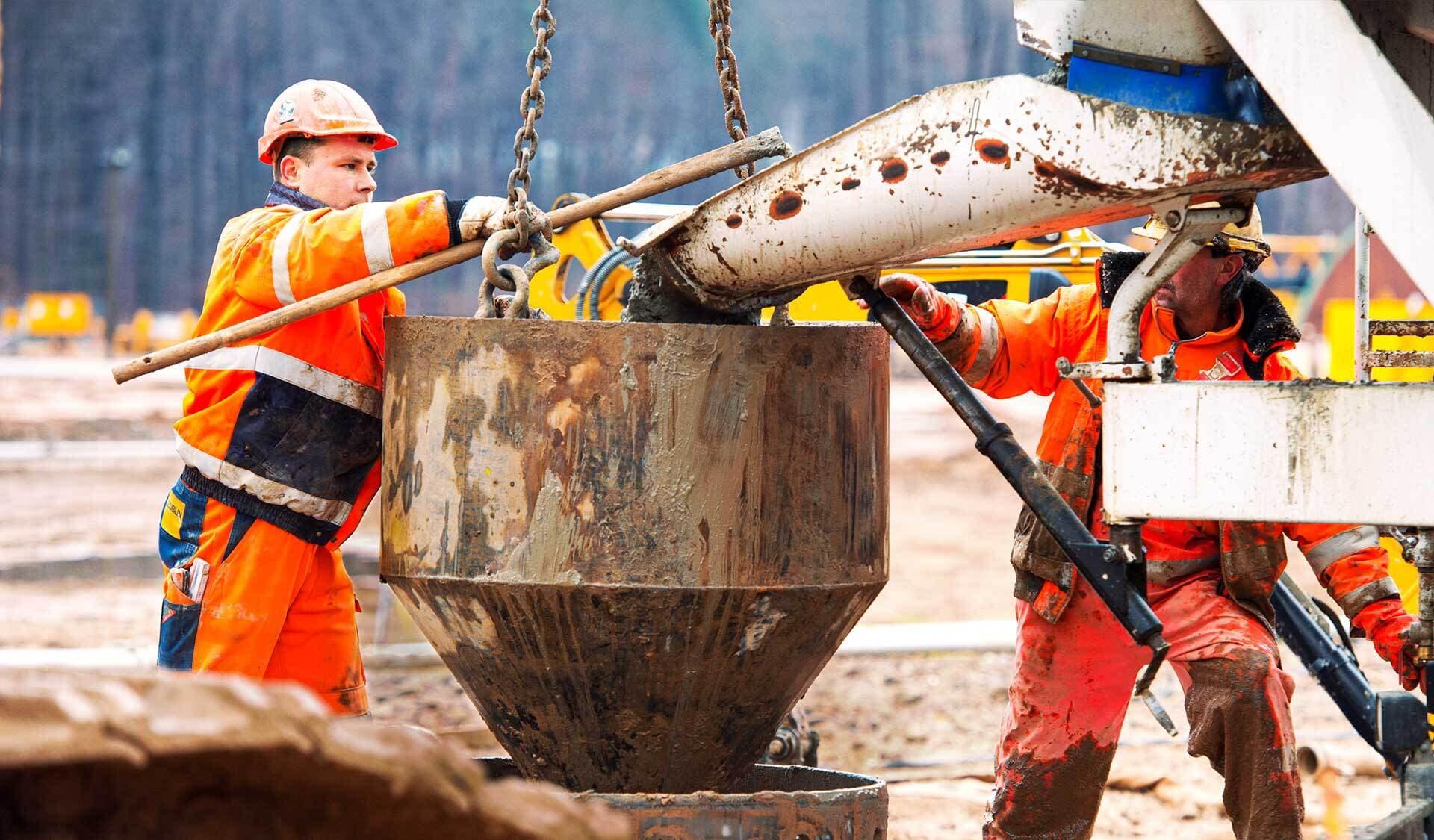 Bauarbeiter füllen Beton ab