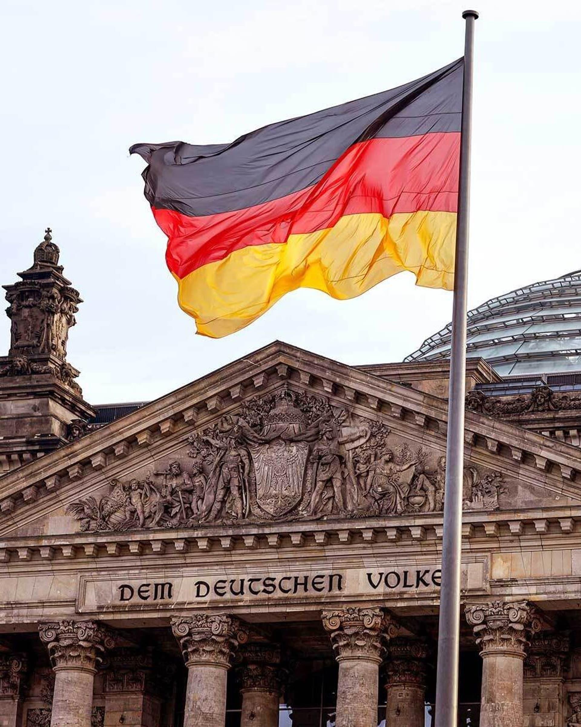 Die deutsche Flagge weht vor dem Reichstag in Berlin