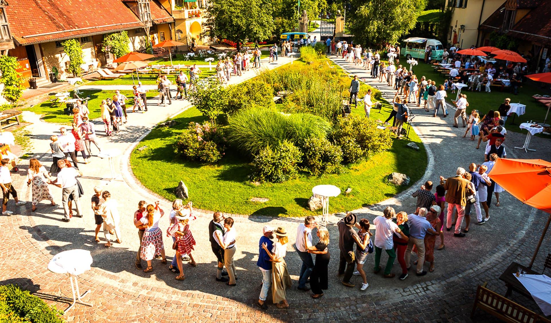 Gäste tanzen ausgelassen in einem Innenhof