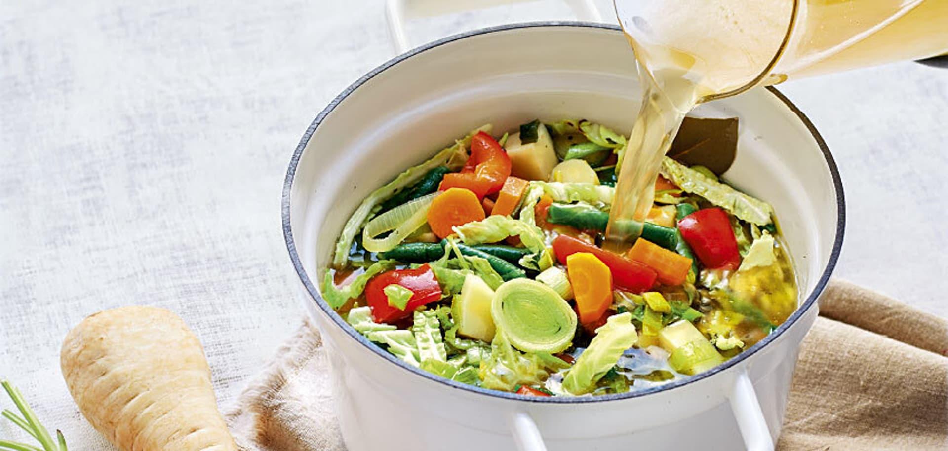 Ein Topf mit Gemüse, in den gerade Brühe gegossen wird