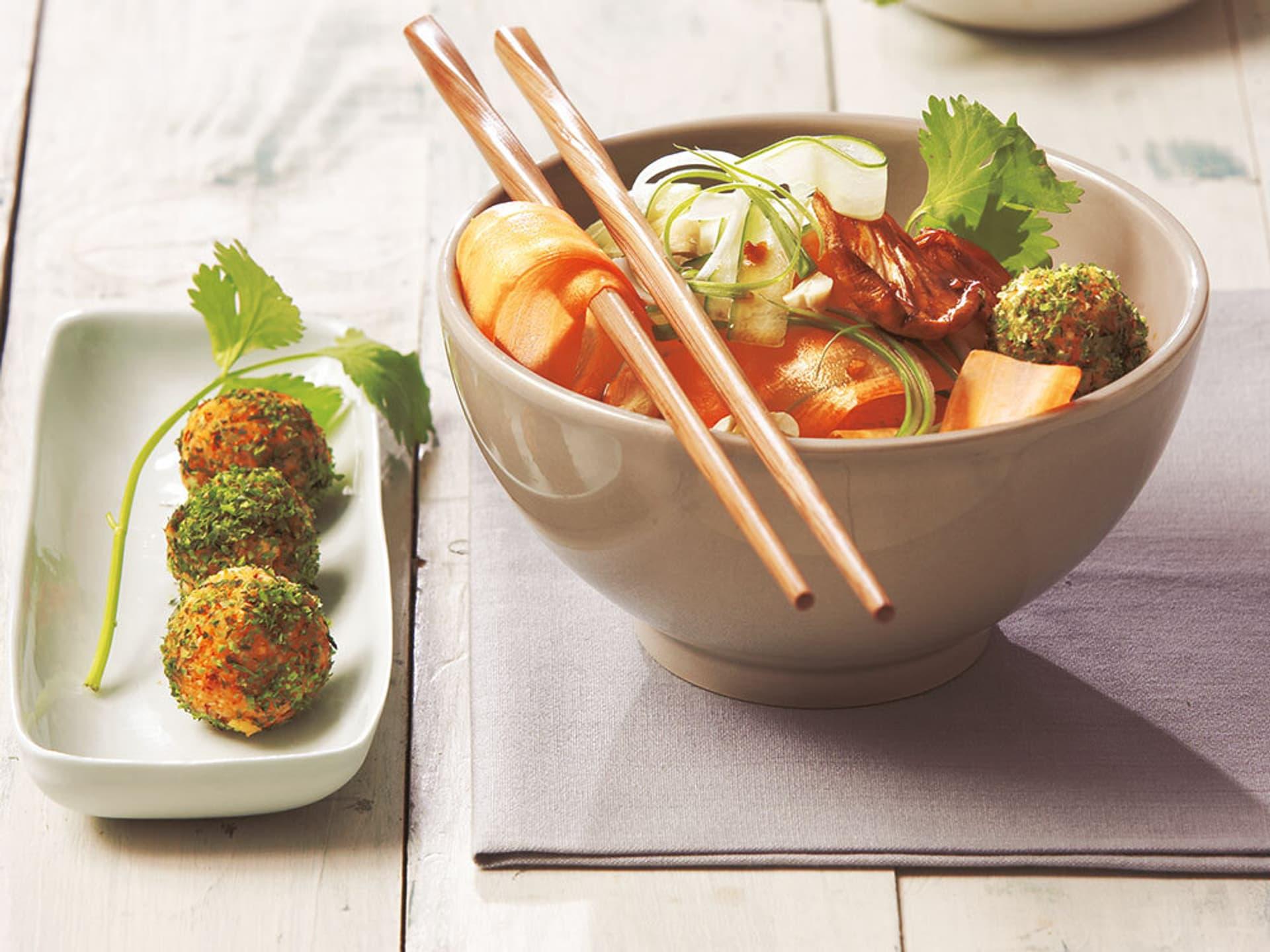 Zwei Schüsseln mit Salat und Bällchen sowie Stäbchen