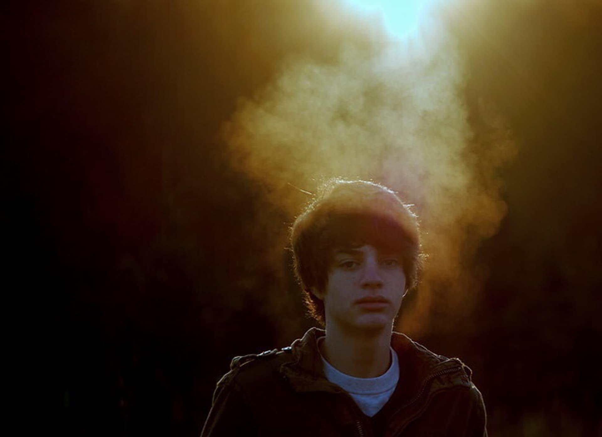 Ein junger Mann im Sonnenaufgang, sein Atem ist im Sonnenlicht erkennbar