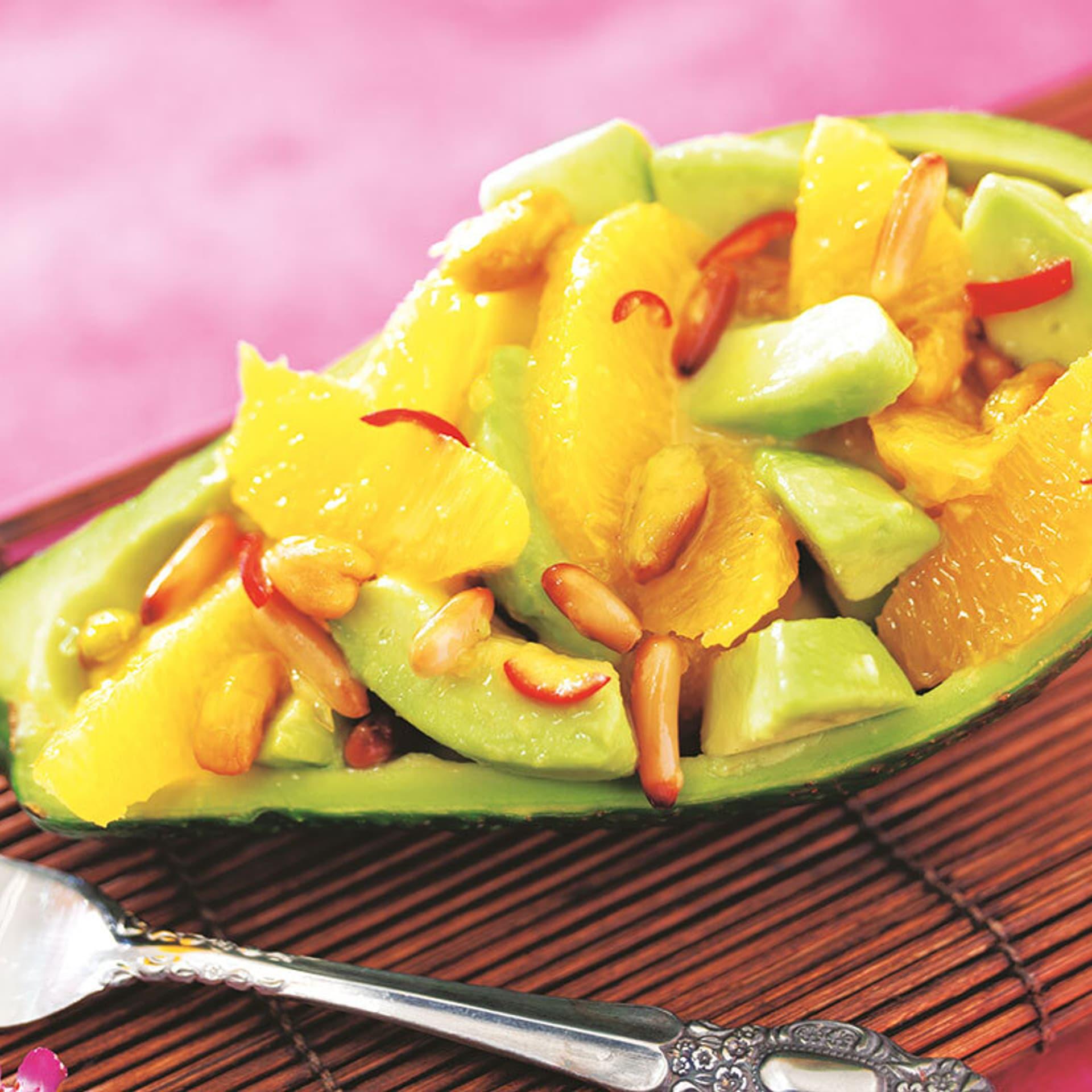 Ein Avocadoschiffen gefüllt mit Orangen und Nüssen