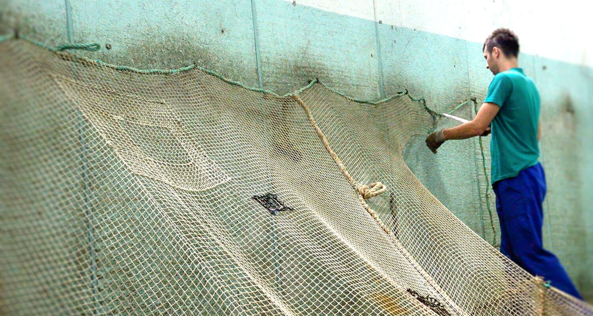 Ein Mann befestigt Fischernetze.