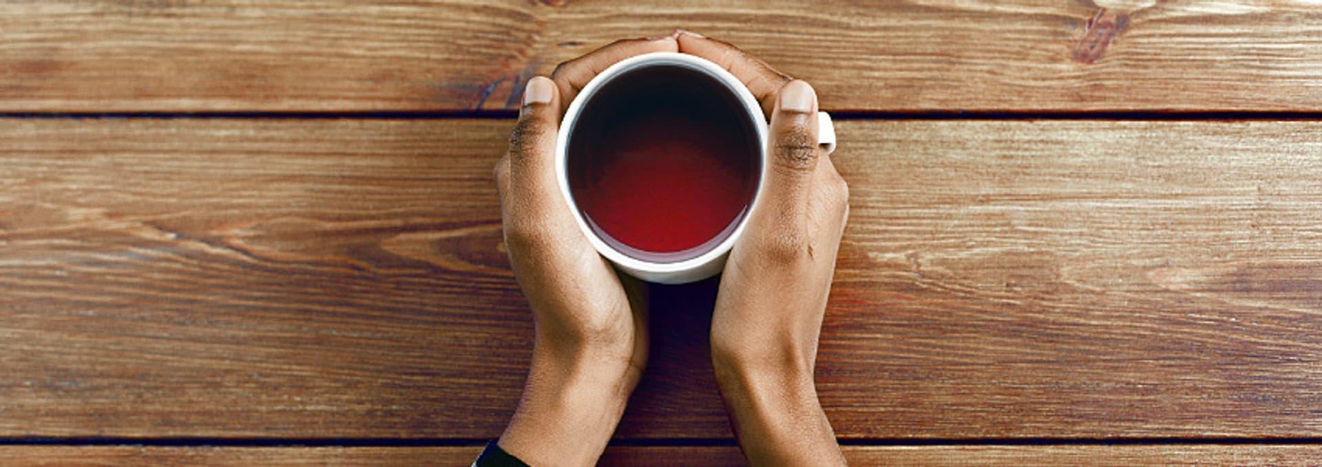 Hände umgreifen eine Tasse mit Tee