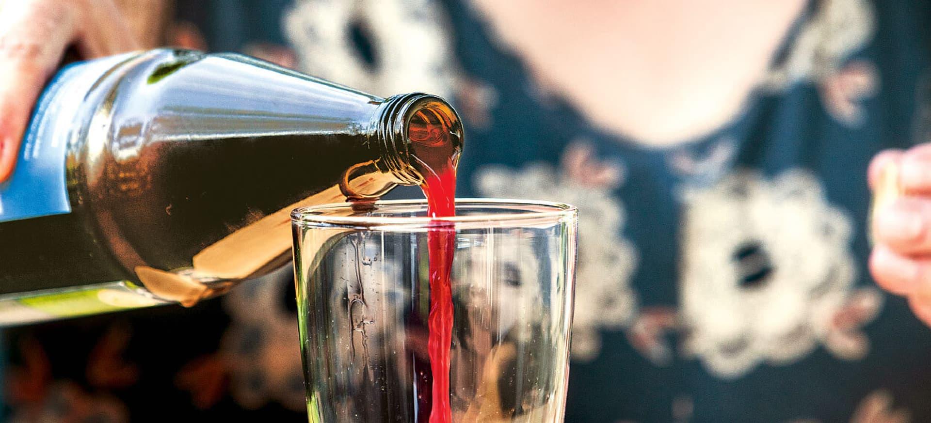 Aus einer Flasche wird rote Flüssigkeit in ein Glas gegossen