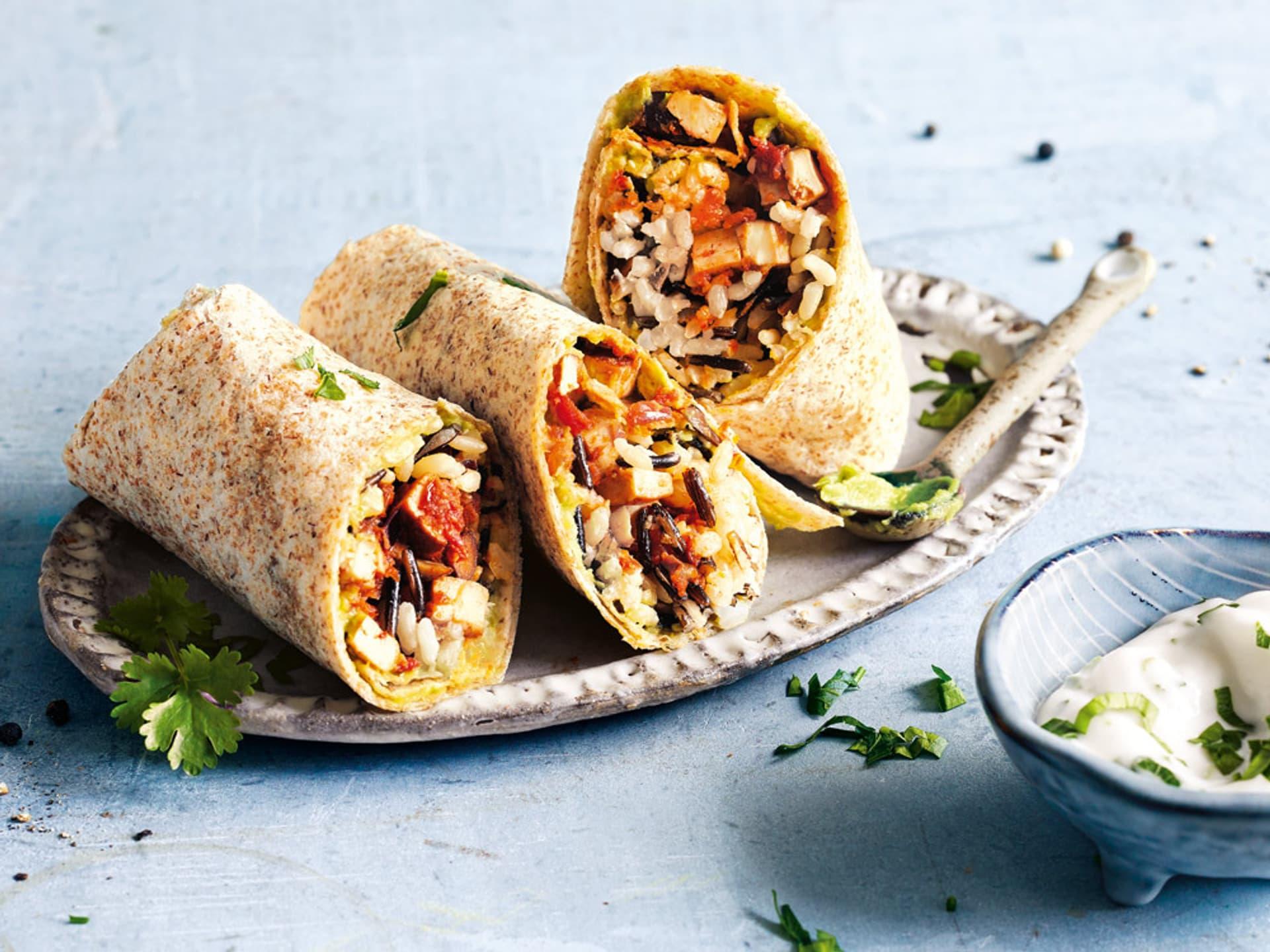 Drei schräg aufgeschnittene Burritos, die gefüllt sind mit buntem Reis, Bohnen und Tofu. Garniert mit Koriander-Blättern.