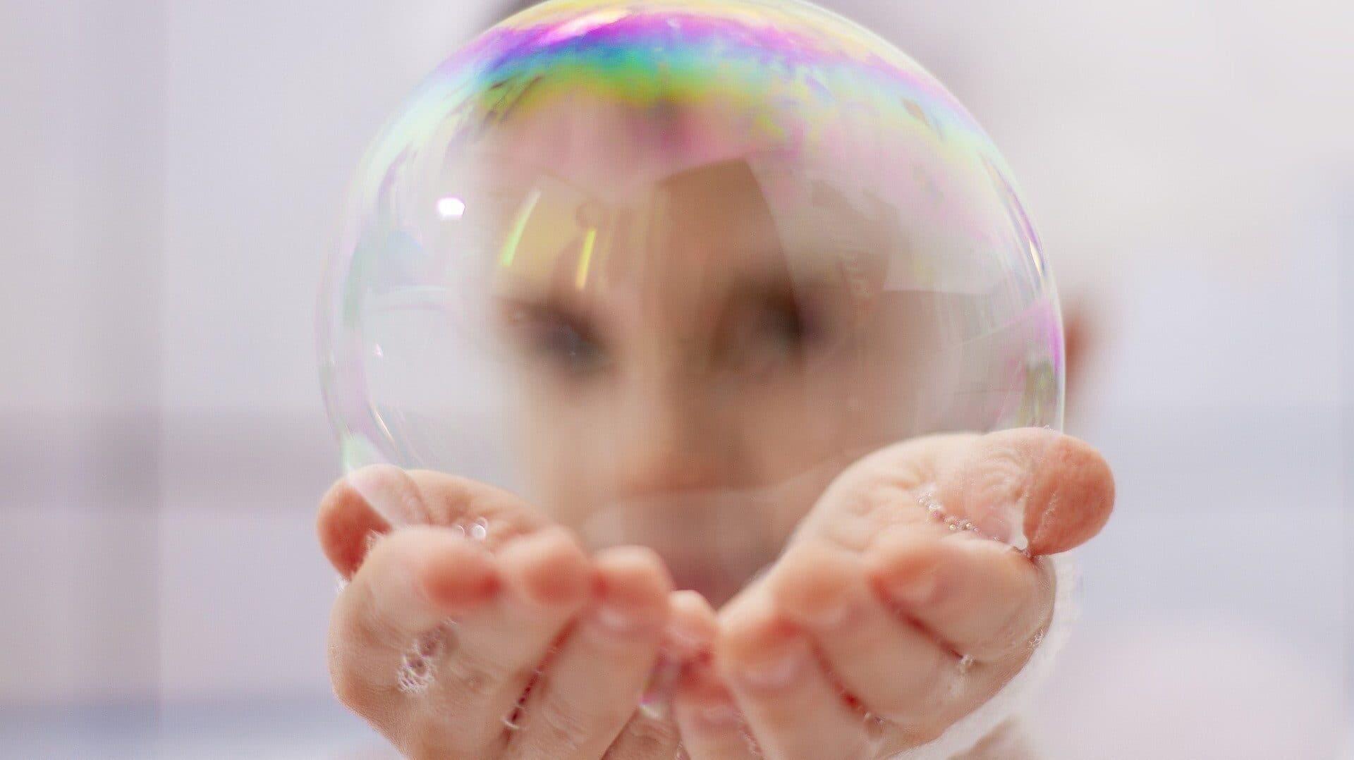 Kind hält eine Seifenblase in beiden Händen