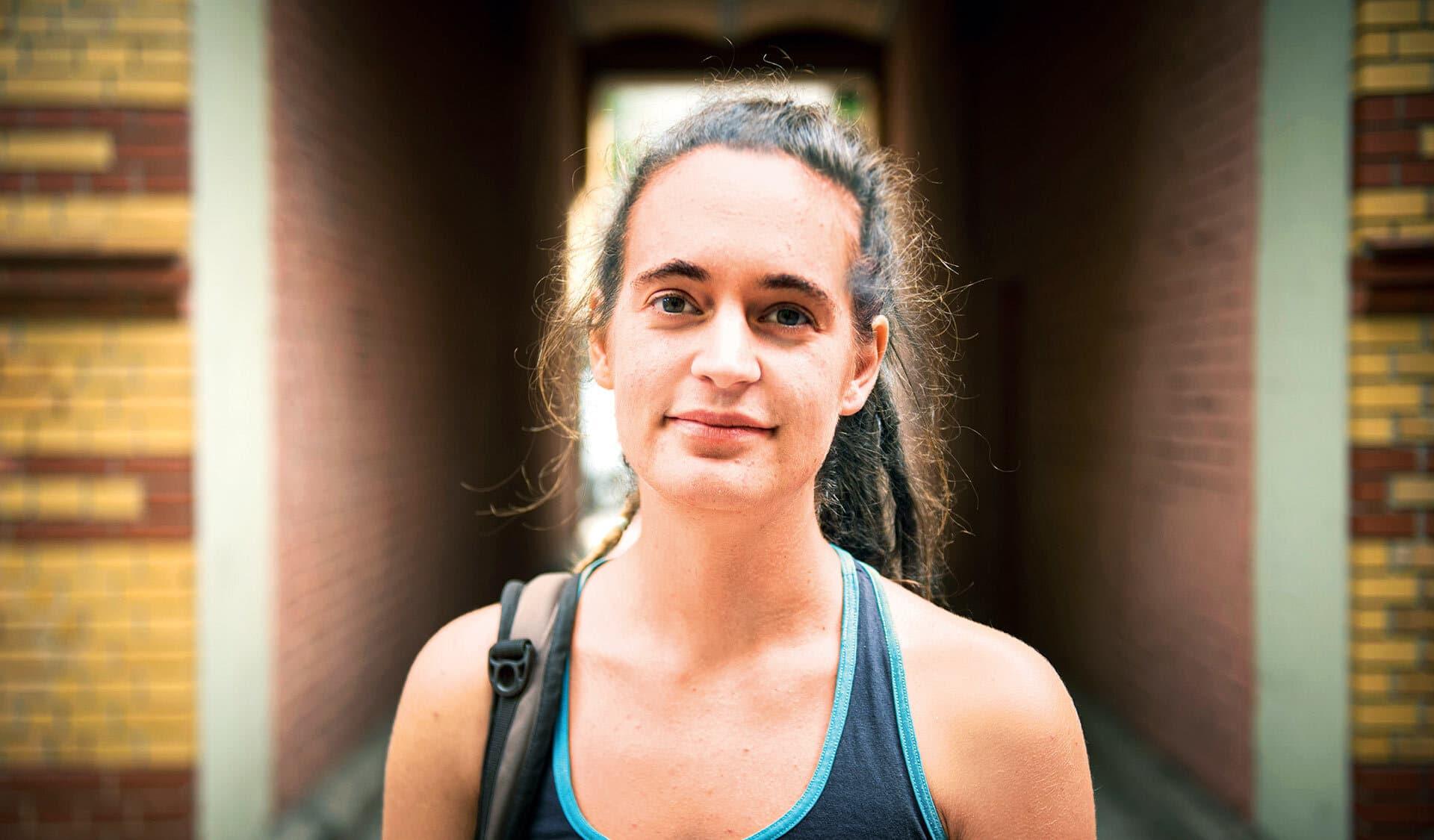 Carola Rackete schaut in die Kamera. Im Hintergrund Häuser mit Durchgang zu Hinterhöfen