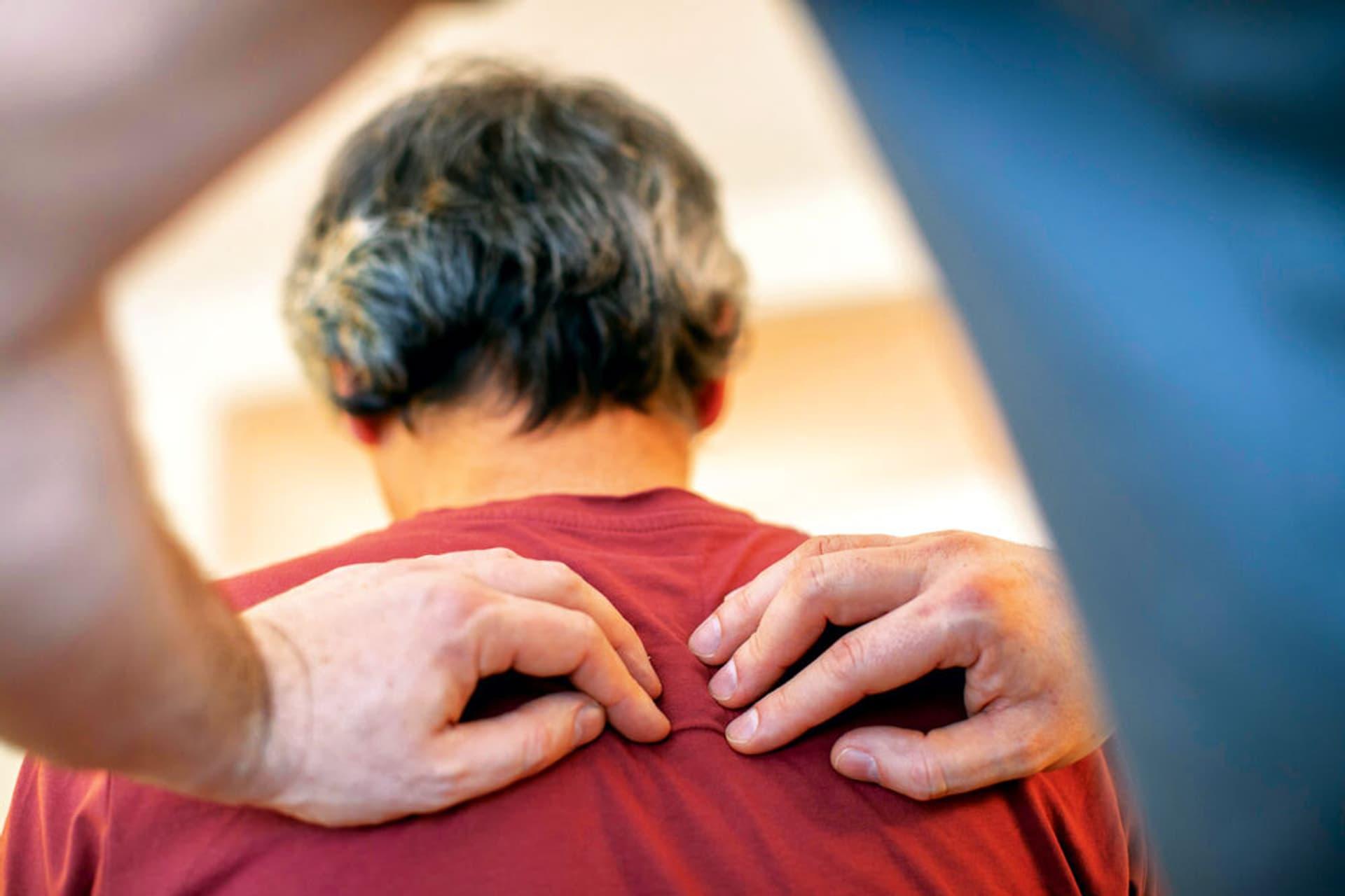 Der Chiropraktiker drückt sanft auf die Brustwirbelsäule des Patienten