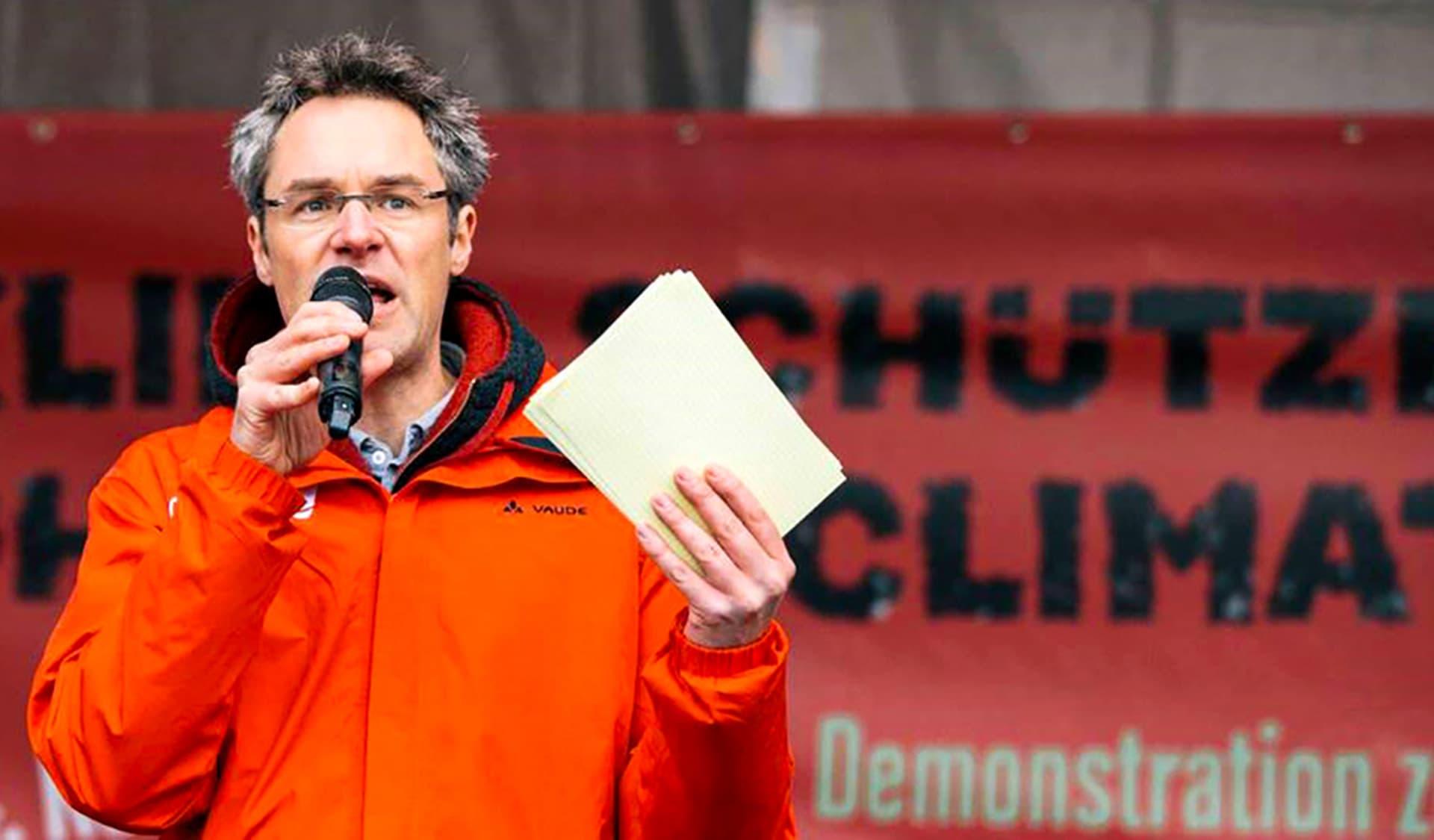 Christoph Bautz von Campact in oranger Jacke mit Mikrofon in der Hand