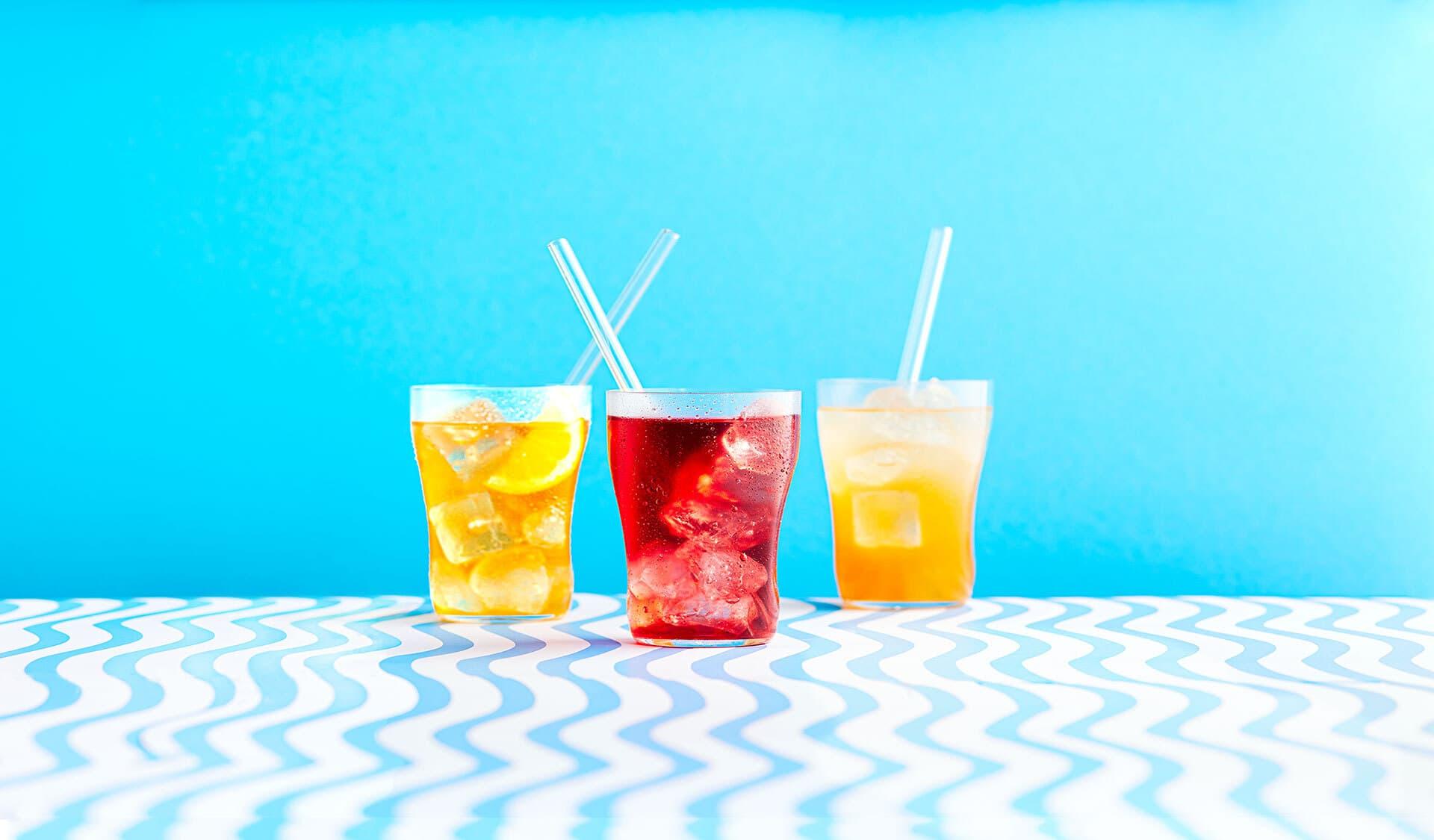 Drei Eistees im Glas mit Trinkhalm