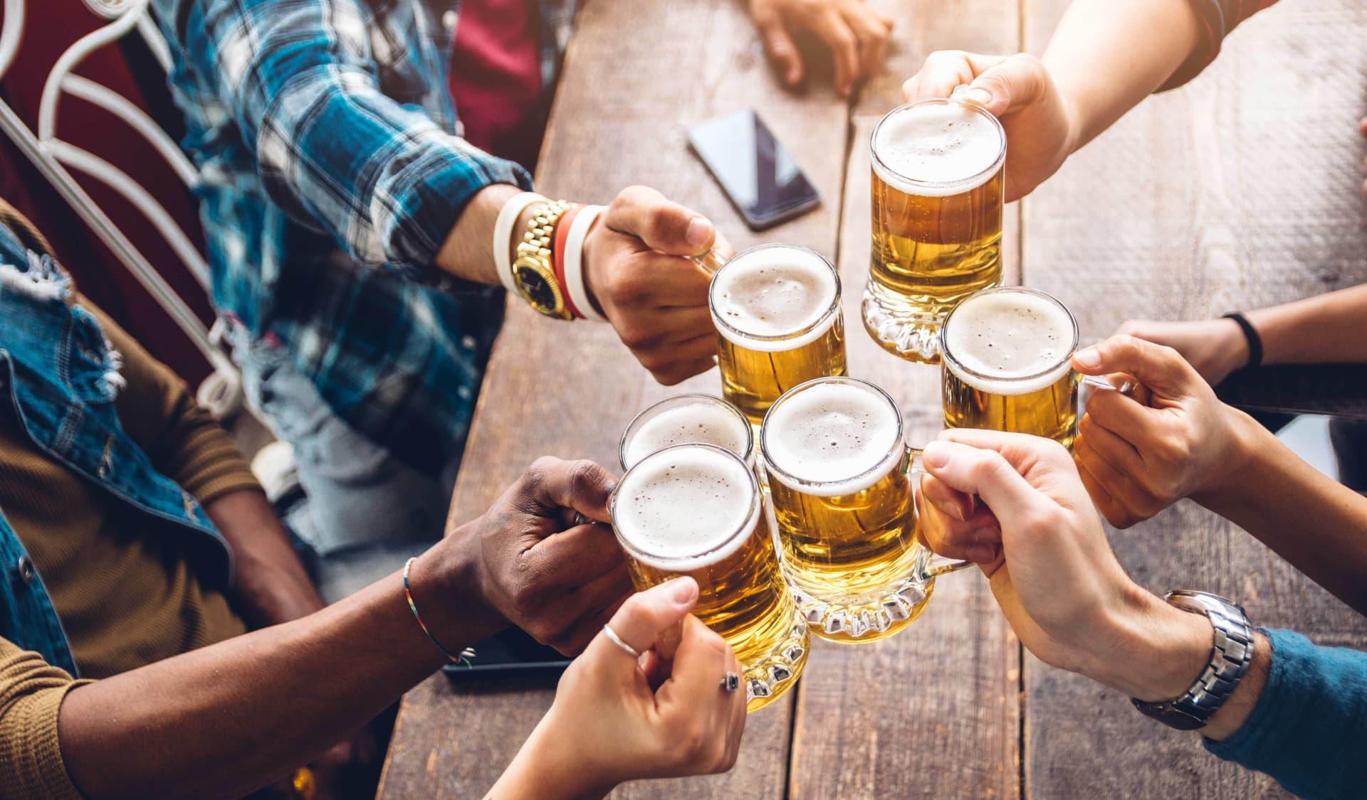 Mehrere Hände halten Biergläser und prosten sich zu.