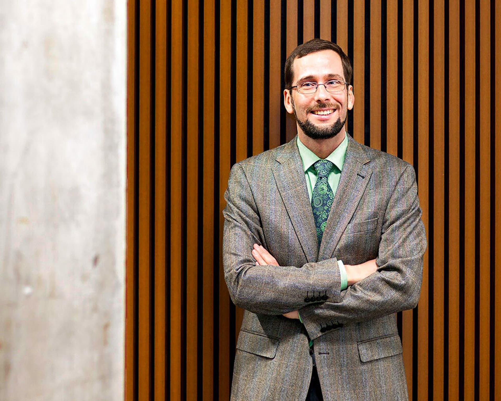 Professor Volker Quaschning steht im Hörsaal vor einer Wand mit verschränkten Armen.