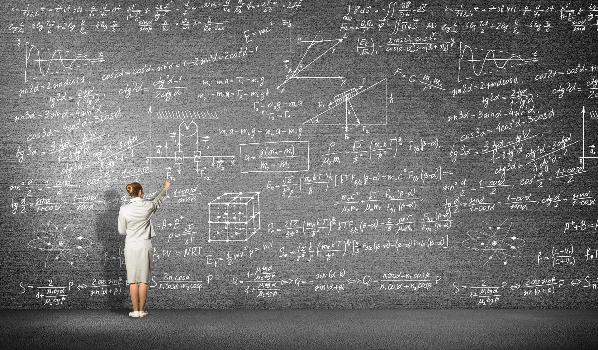 Eine Frau steht vor einer Tafel und schreibt Formeln auf