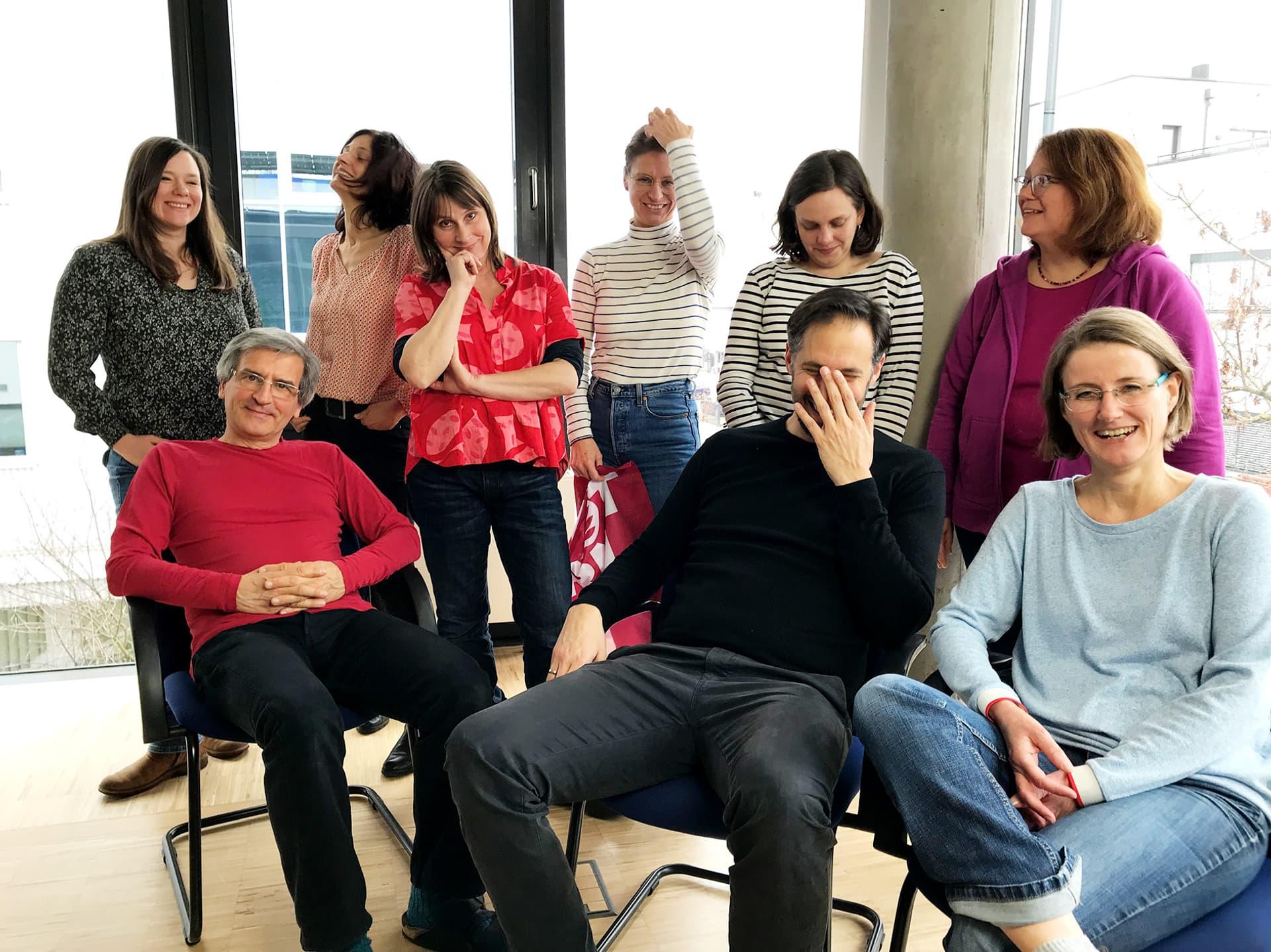 Neun Redakteurinnen und Redakteure der Schrot&Korn stehen in einem gläsernen Büro.
